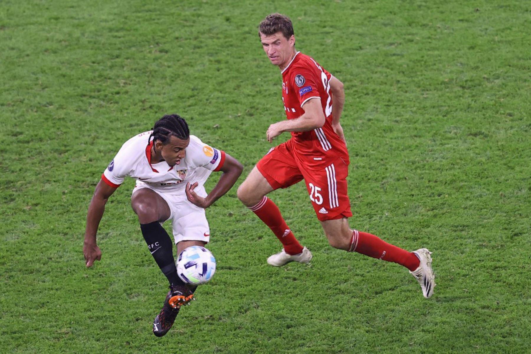El defensor francés del Sevilla Jules Kounde y el delantero alemán del Bayern Munich Thomas Mueller compiten por el balón durante el partido de fútbol de la Supercopa de la UEFA entre el FC Bayern Munich y el Sevilla FC en el Puskas Arena en Budapest, Hungría. Foto: AFP