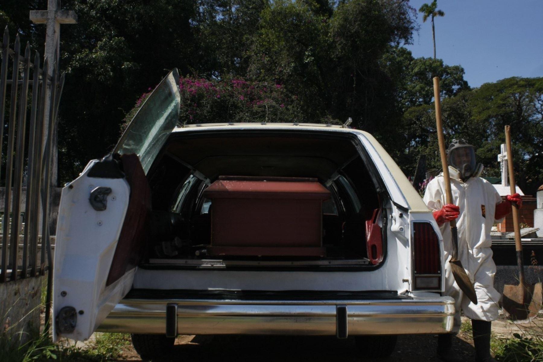 Trabajadores gubernamentales se disponen a bajar un ataúd con una víctima de covid-19 de un vehículo para proceder a enterrarlo en San Cristóbal, Venezuela. Foto: EFE