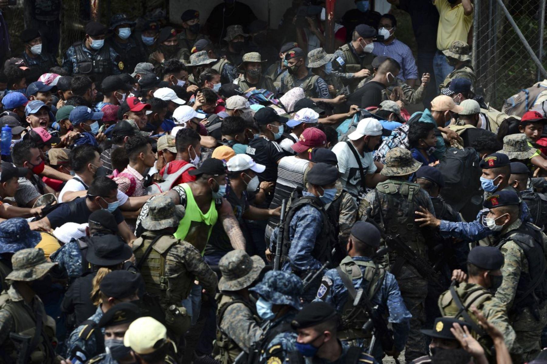 Migrantes hondureños rompen la valla policial para ingresar a Guatemala en su camino a los Estados Unidos, en la frontera de Corinto, Honduras, el 1 de octubre de 2020. La caravana salió de San Pedro Sula el miércoles a la medianoche en búsqueda del sueño americano. Foto: AFP