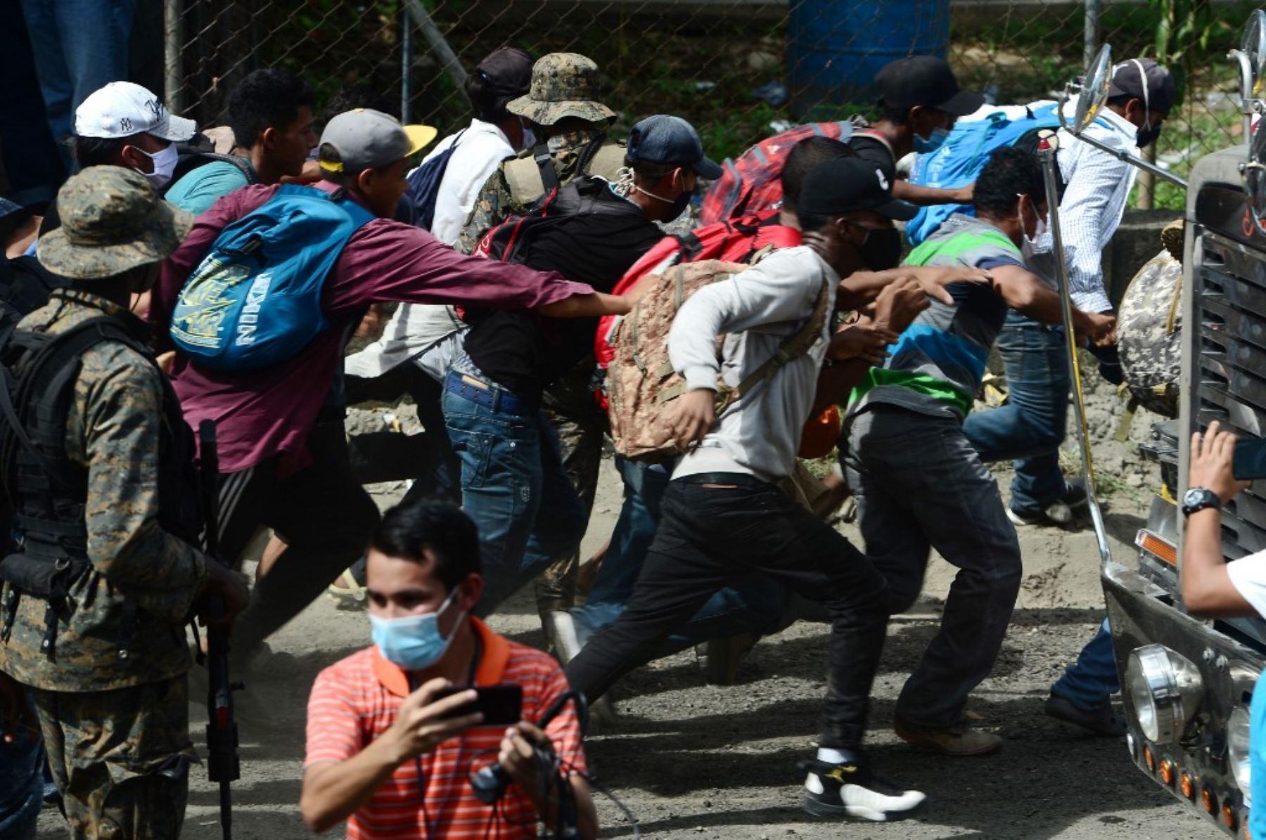 Migrantes hondureños rompen la valla policial para ingresar a Guatemala en su camino a los Estados Unidos, en la frontera de Corinto, Honduras. Foto: AFP