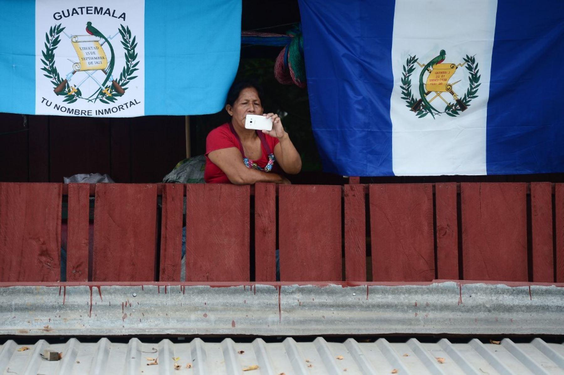 Una mujer bajo banderas guatemaltecas y hondureñas, registra como migrantes hondureños rompen la valla policial para ingresar a Guatemala en su camino a los Estados Unidos, en la frontera de Corinto, Honduras. Foto: AFP