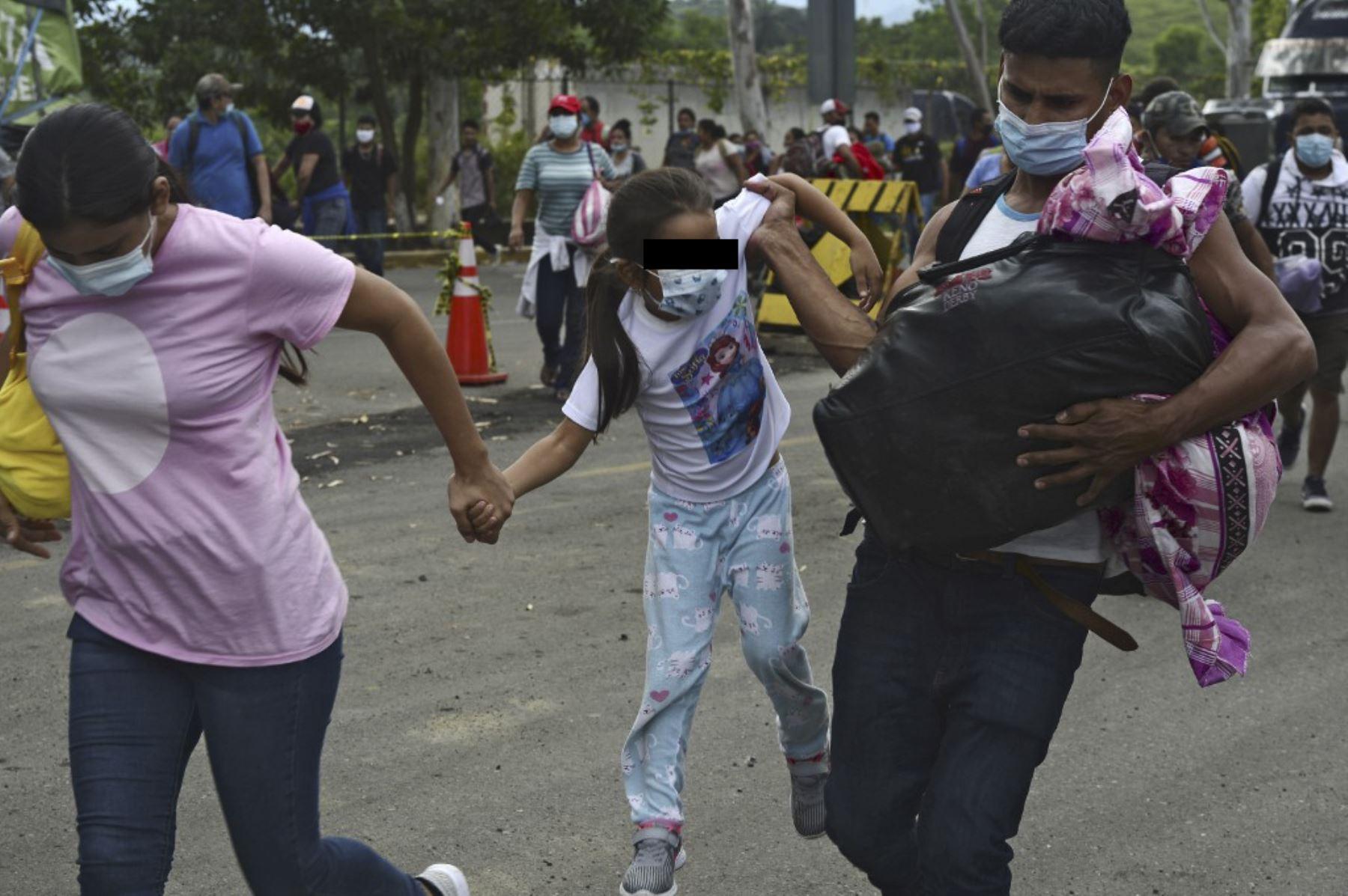 Una pareja de migrantes hondureños y su hija atraviesan una cerca policial para ingresar a Guatemala en su camino a los Estados Unidos, en la frontera de Corinto, Honduras. Foto: AFP