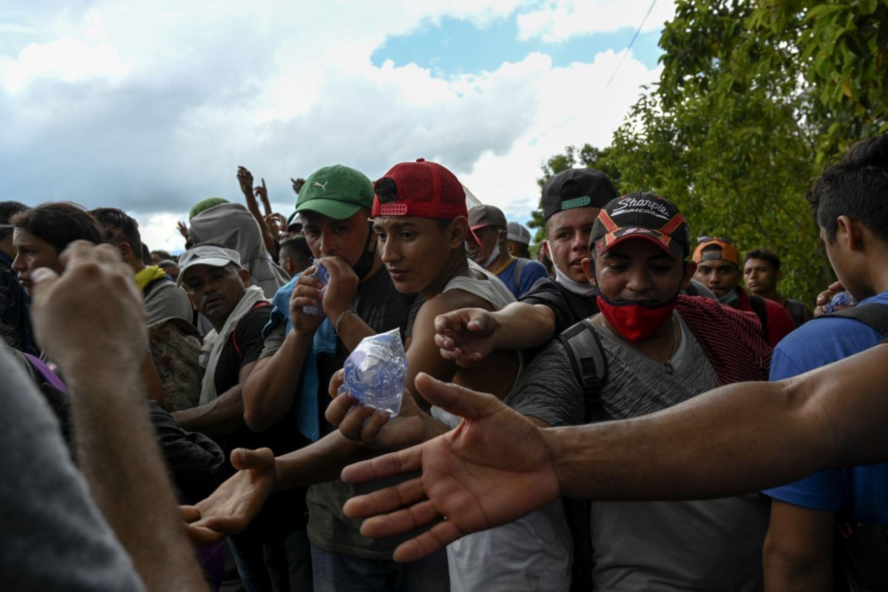 Migrantes hondureños, parte de una caravana rumbo a Estados Unidos, buscan agua que les entregan miembros del Ejército de Guatemala, en Entre Ríos, Guatemala, luego de cruzar la frontera de Honduras. Foto: AFP