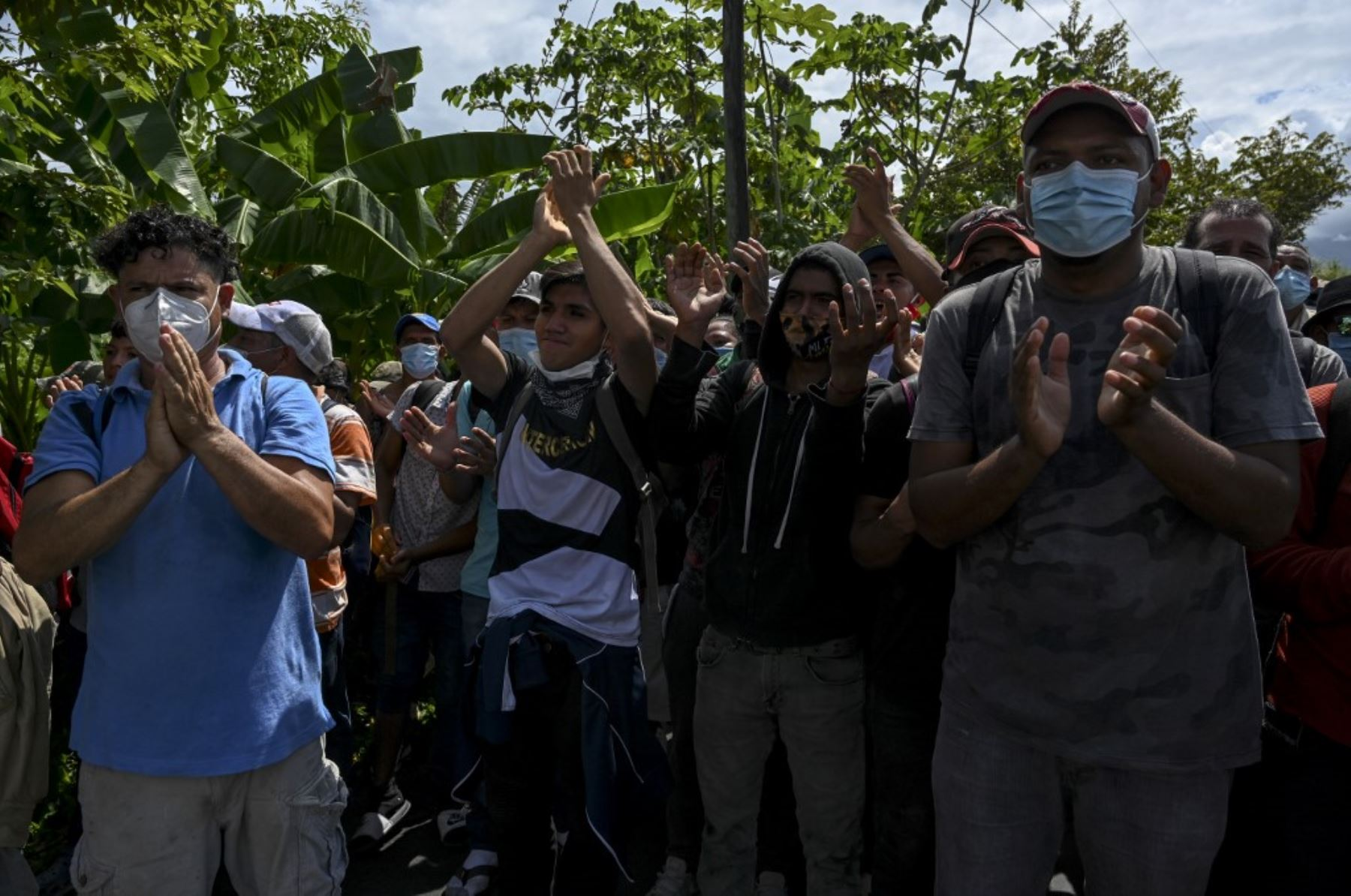 Los migrantes hondureños, parte de una caravana rumbo a Estados Unidos, aplauden a los miembros del Ejército de Guatemala que los dejaron pasar, en Entre Ríos, Guatemala, luego de cruzar la frontera de Honduras. Foto: AFP