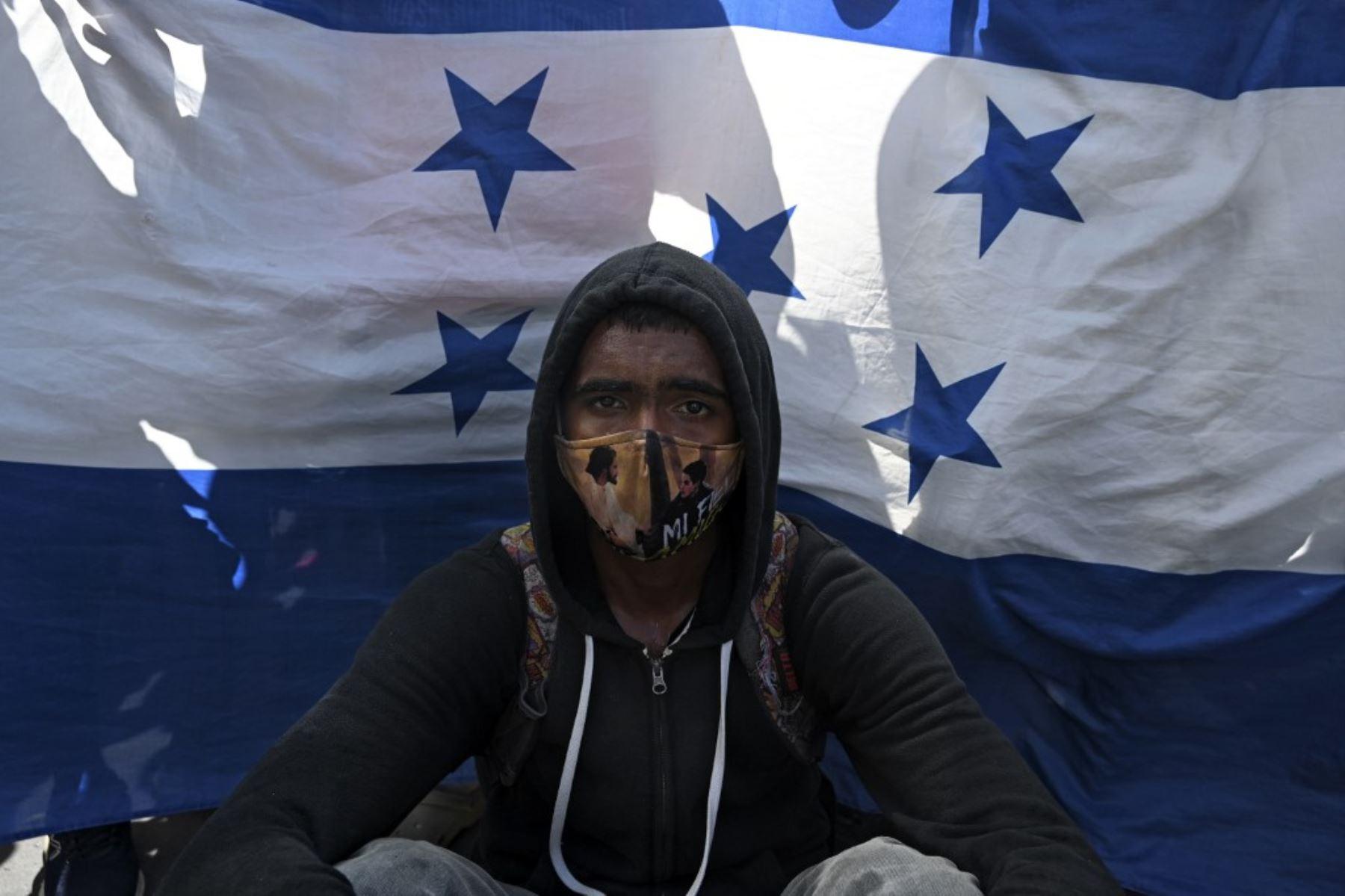 Un migrante hondureño se sienta frente a una bandera hondureña en Entre Ríos, Guatemala, luego de cruzar la frontera de Honduras en su camino a los Estados Unidos en una caravana. Foto: AFP