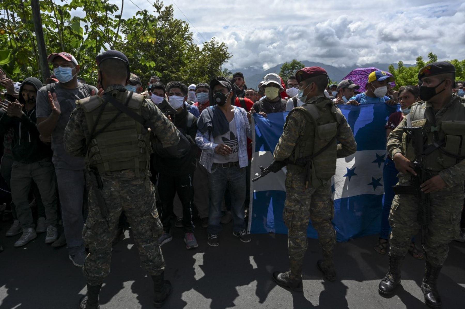 Miembros del Ejército de Guatemala detienen a un grupo de migrantes hondureños que portaban una bandera hondureña en Entre Ríos, Guatemala, después de que cruzaron la frontera de Honduras en su camino a los EE. UU. Foto: AFP