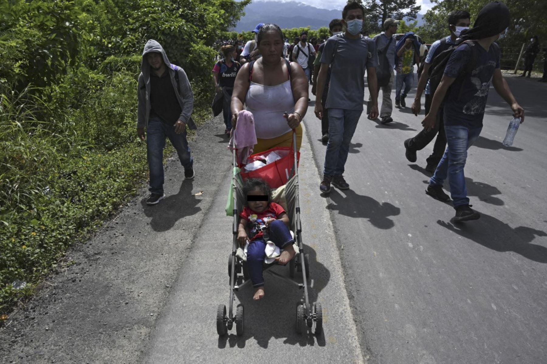 Un migrante hondureño, parte de una caravana que se dirige a Estados Unidos, empuja a un niño en un tranvía en Entre Ríos, Guatemala, luego de cruzar la frontera de Honduras. Foto: AFP