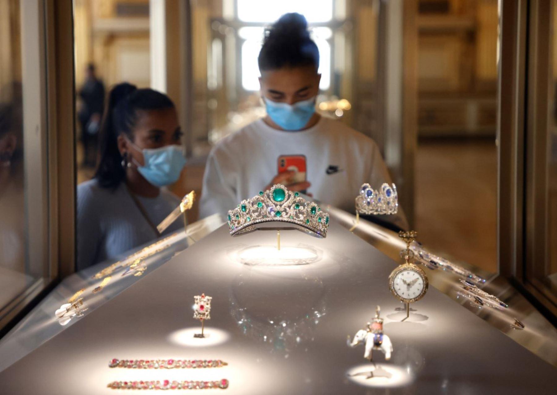 Visitantes con mascarillas miran la Diadema de la Duquesa de Angulema expuesta en una ventana que se exhibe en la galería Apolo del Museo del Louvre, abandonada por los turistas debido a la pandemia de Covid-19, en París. Foto: AFP