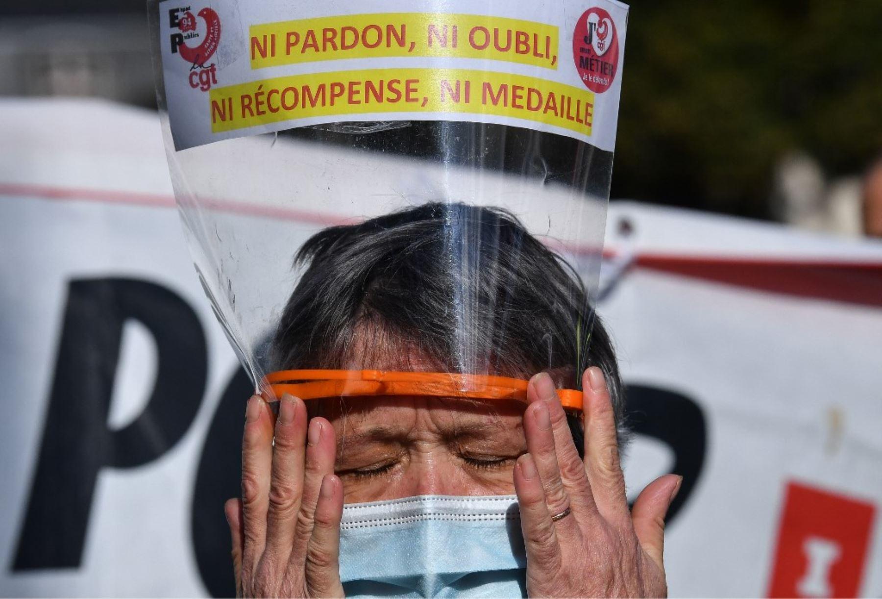 Una enfermera usa una mascarilla protectora y una visera que dice,