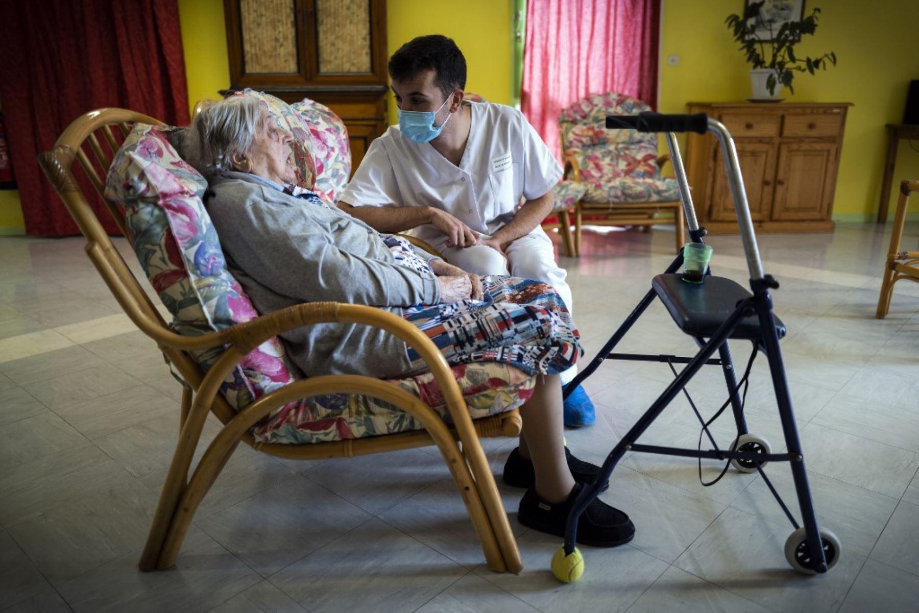 Rosalie Jalbert, de 102 años, que dio positivo en la prueba del Covid-19, conversa con un empleado mientras se sienta en un sofá en la casa de retiro Le Coustil en Salles, sur de Francia. Foto: AFP