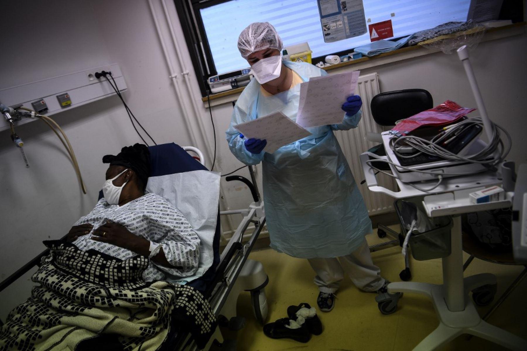 Una enfermera revisa los documentos mientras está de pie junto a una mujer que yace en una cama y se sospecha que está infectada con Covid-19 en el servicio de emergencia del hospital Andre Gregoire en Montreuil, al este de París. Foto: AFP