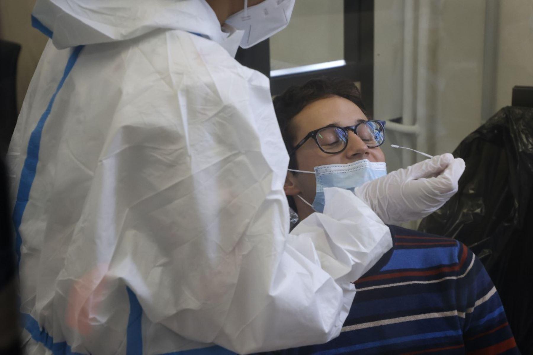 Un personal médico realiza una prueba a un estudiante en un centro de pruebas Covid-19 ubicado en el antiguo Ayuntamiento del distrito 4. Foto: AFP