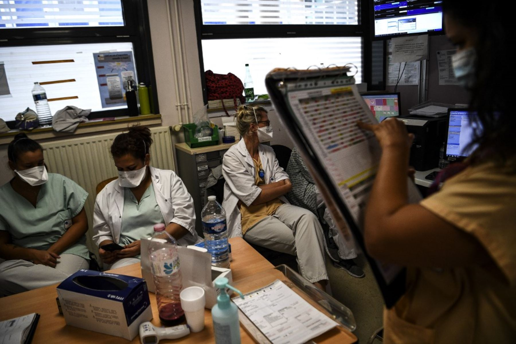 Los trabajadores médicos verifican la información en sus teléfonos y un gráfico en el servicio de emergencia del hospital Andre Gregoire en Montreuil, al este de París. Foto: AFP