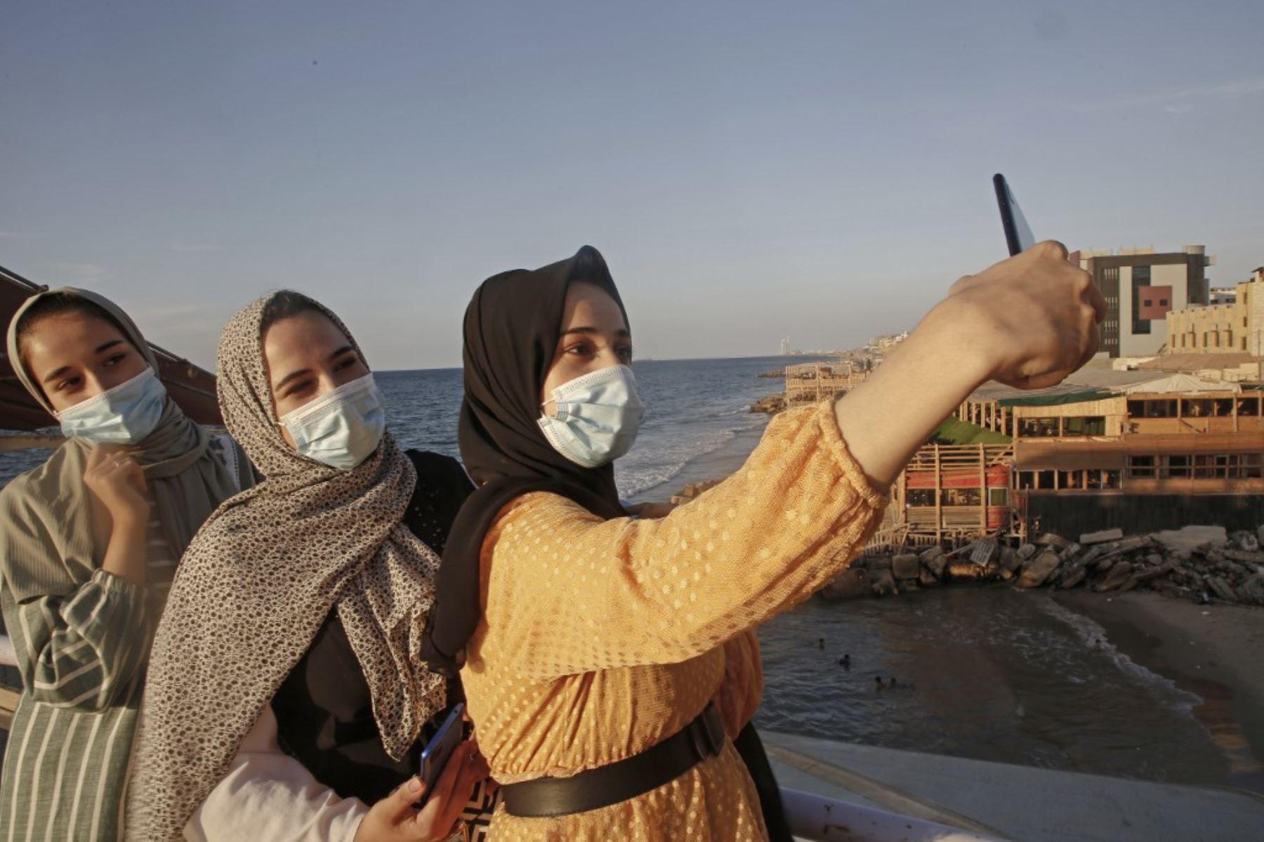 Mujeres palestinas se toman una selfie al atardecer en la ciudad de Gaza en medio de estrictas restricciones debido a la pandemia de COVID-19 el 12 de octubre de 2020. Foto: AFP