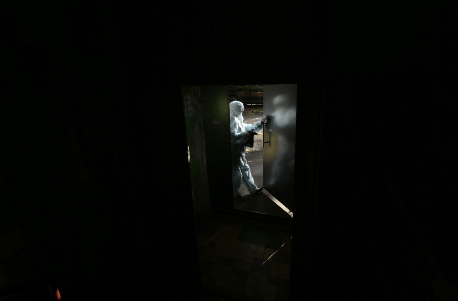 Un trabajador comunal con equipo de protección personal (EPP) rocía desinfectante en la puerta de un edificio residencial en Moscú. Foto: AFP