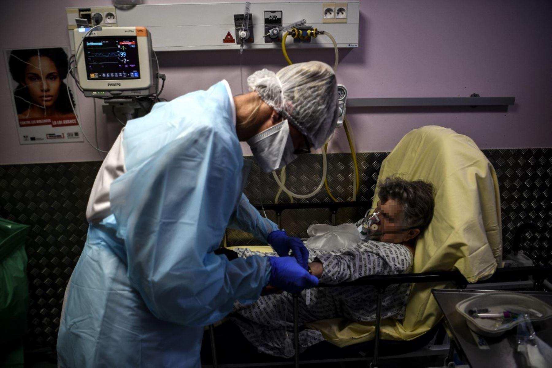 Una enfermera atiende a una anciana sospechosa de estar infectada con Covid-19 en el servicio de emergencia del hospital Andre Gregoire en Montreuil, al este de París. Foto: AFP