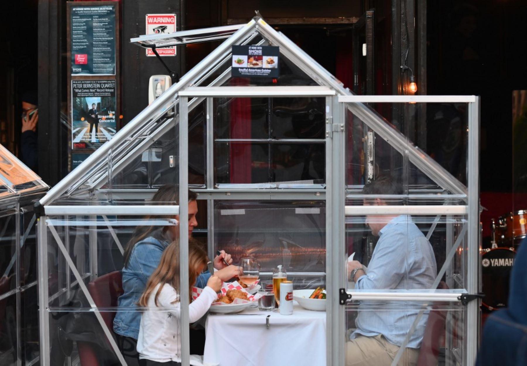 La gente cena en carpas de plástico por distanciamiento social en un restaurante en Manhattan en la ciudad de Nueva York, en medio de la pandemia de coronavirus. Foto: AFP