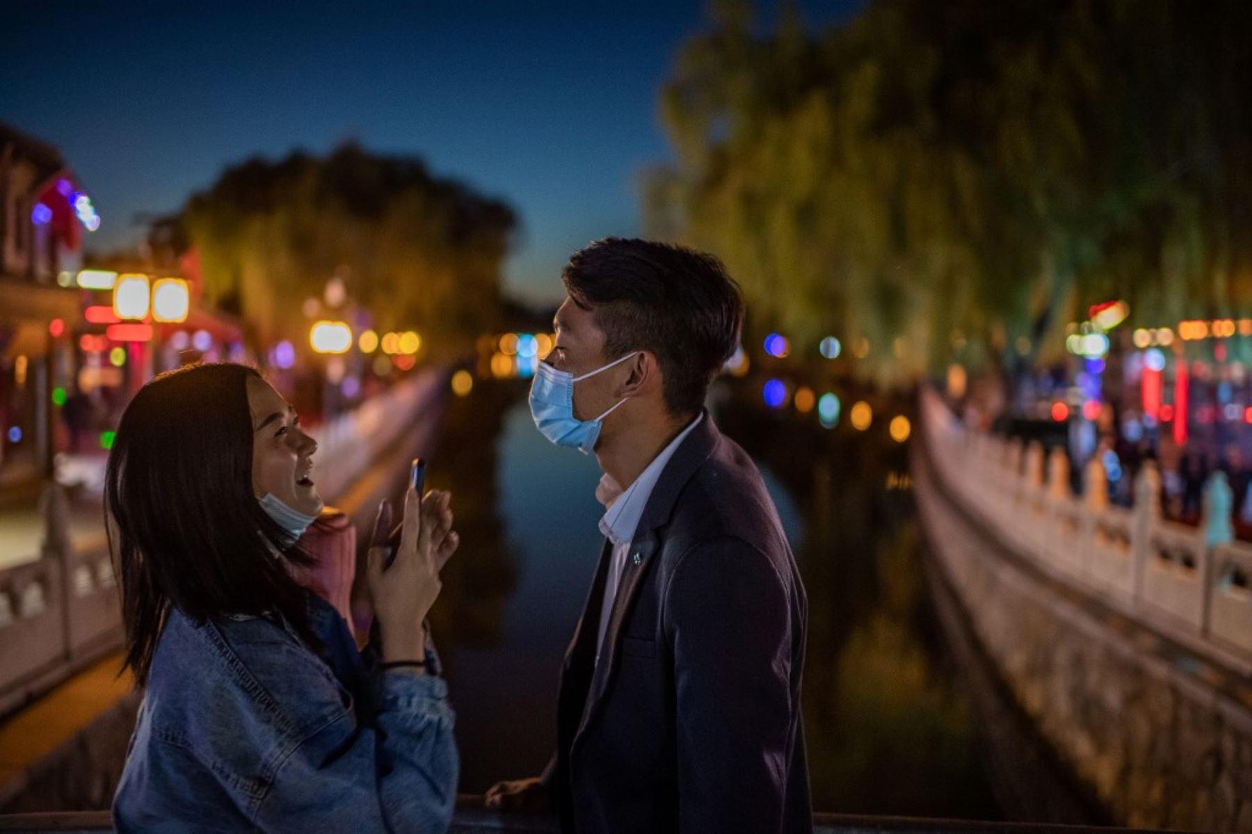 Una pareja que usa máscaras faciales como medida preventiva contra el Covid-19 se ríe mientras se toman fotos con un teléfono en un puente en el lago Hu Hai en Beijing. Foto: AFP
