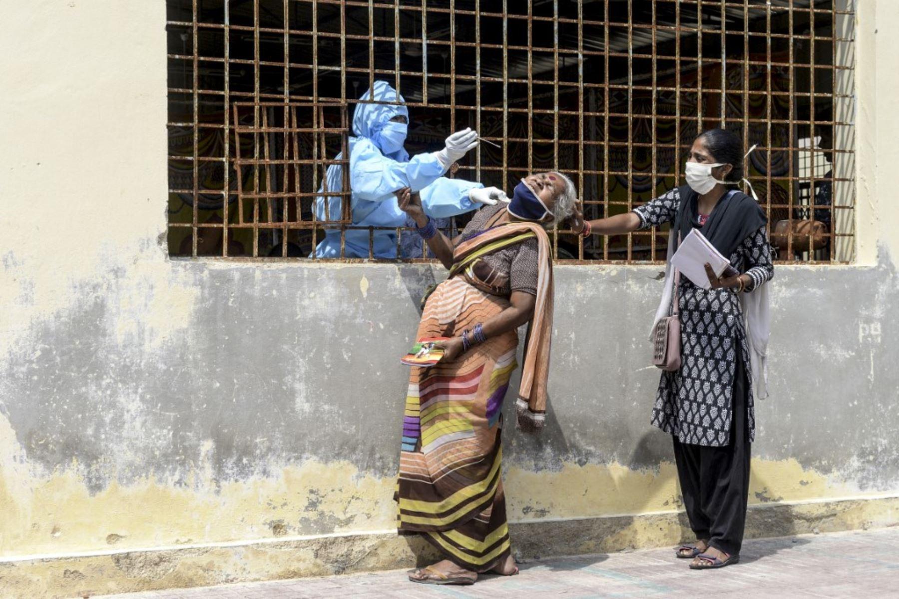 Una mujer reacciona cuando una trabajadora de salud le toma una muestra de hisopo para realizar una prueba del coronavirus Covid-19 antes de ir a un campamento médico para víctimas de inundaciones en un barrio pobre después de las fuertes lluvias en Hyderabad. Foto: AFP