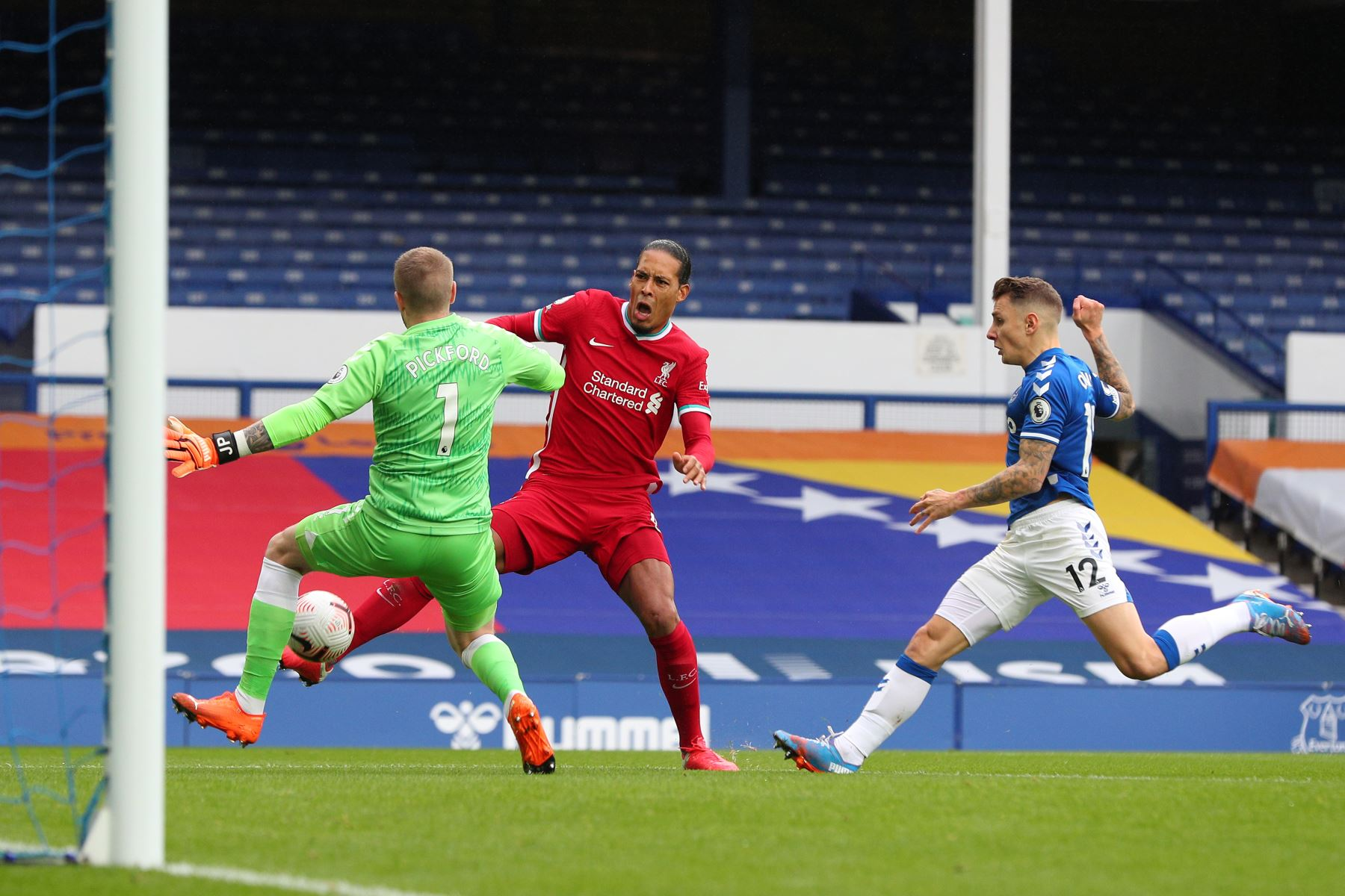 El portero inglés de Everton, Jordan Pickford, aborda al defensor holandés de Liverpool Virgil van Dijk durante el partido de fútbol de la Premier League en Goodison Park, Liverpool. Foto: AFP
