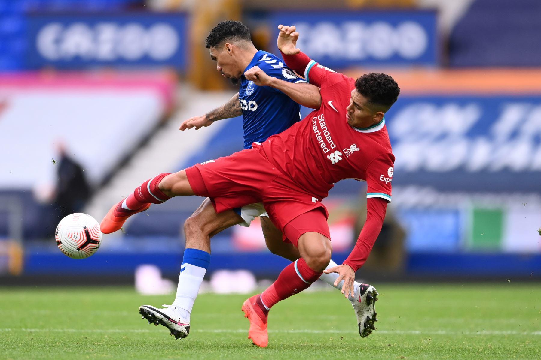 El mediocampista brasileño del Liverpool, Roberto Firmino, compite con el mediocampista brasileño del Everton, Allan, durante el partido de fútbol de la Premier League en Goodison Park, Liverpool. Foto: AFP