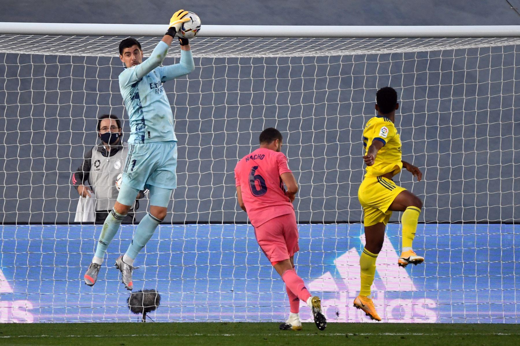 El portero belga del Real Madrid, Thibaut Courtois, salta para atrapar el balón durante el partido de fútbol de la Liga española en el estadio Alfredo Di Stefano, en Valdebebas, noreste de Madrid. Foto: AFP