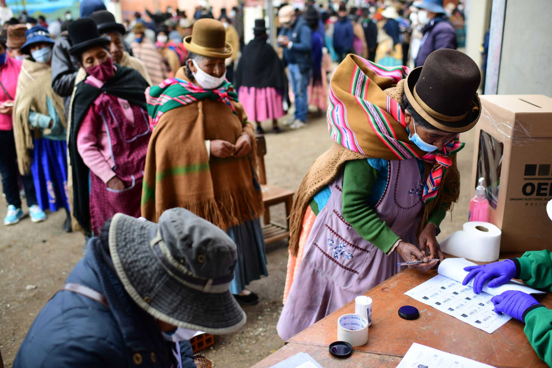 Una mujer indígena firma después de emitir su voto en un colegio electoral en Huarina, Bolivia, durante las elecciones generales que se desarrollan en medio de la pandemia por coronavirus. Foto: AFP
