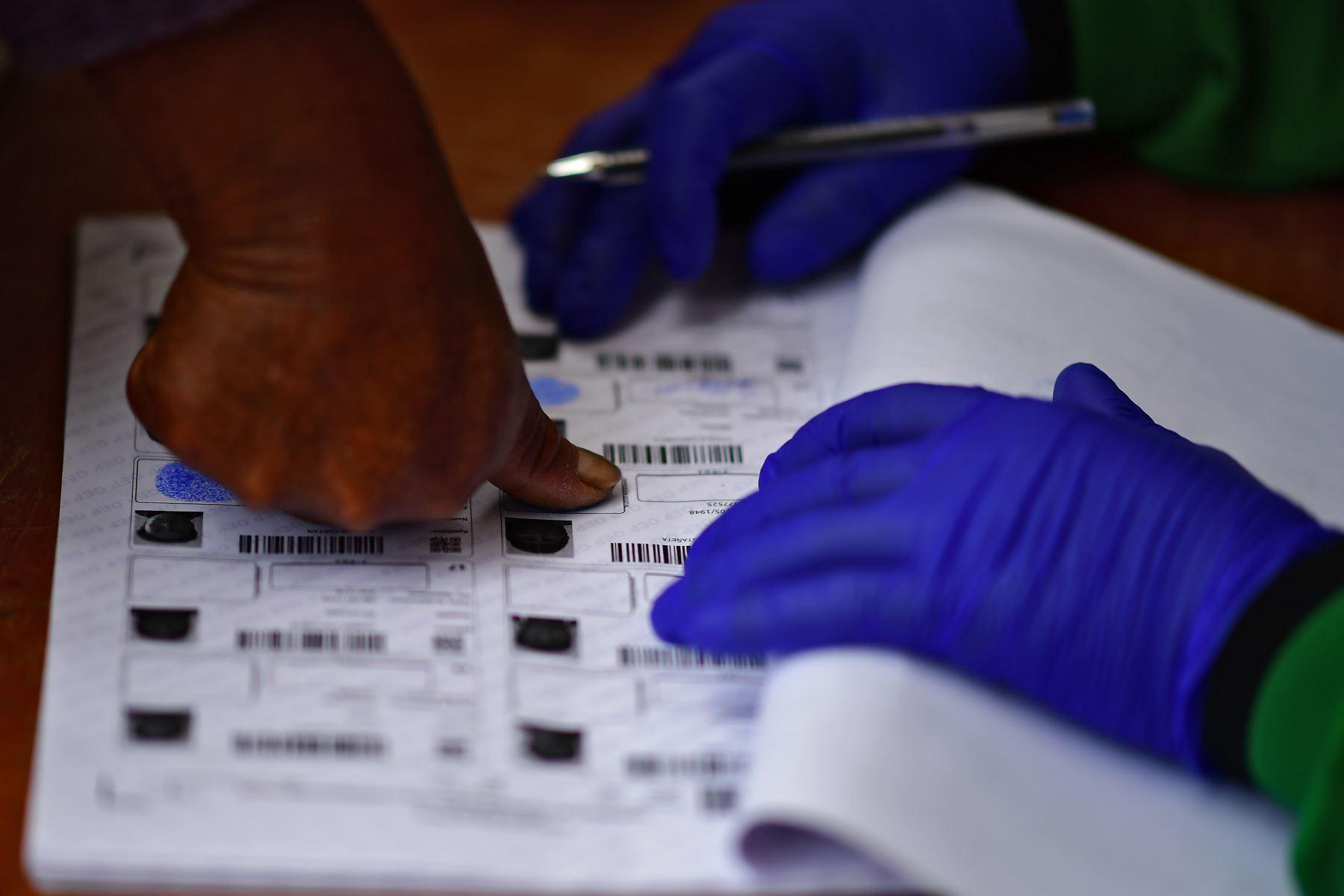 Una persona estampa su huella después de emitir su voto en un colegio electoral en Huarina, Bolivia, durante las elecciones generales en medio de la pandemia. Foto: AFP