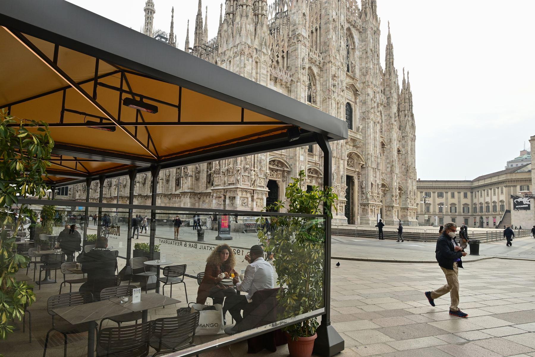 Personas con mascarillas transitan por la Catedral de Milán mientras algunos visitan restaurantes en medio del rebrote por coronavirus. Foto: AFP