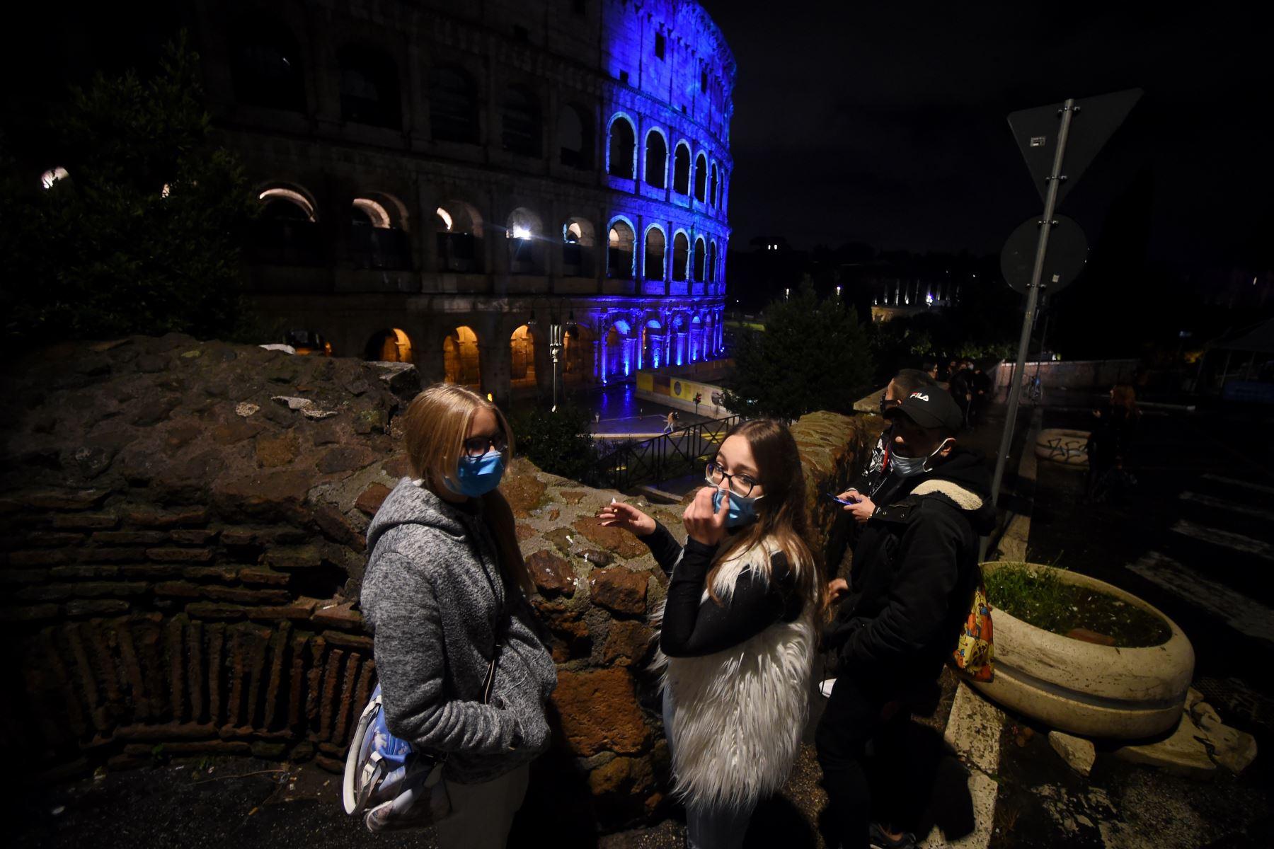 Las personas que llevan máscaras faciales dialogan junto al coliseo que se ilumina por el 75 aniversario de la FAO, en el centro de Roma. Foto: AFP