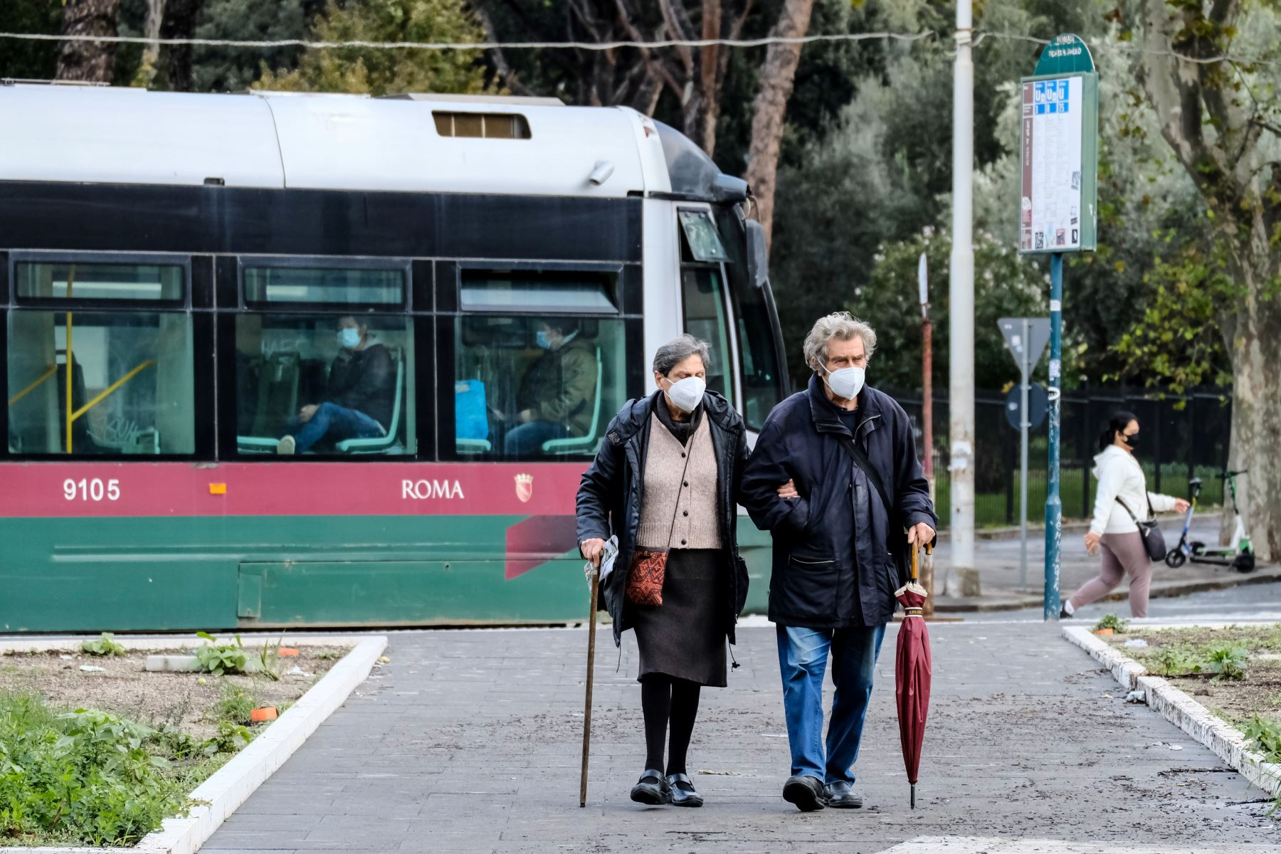 Una pareja de ancianos con mascarillas protectoras, se aleja de la parada del tranvía en medio de la pandemia, en Roma. Foto: AFP