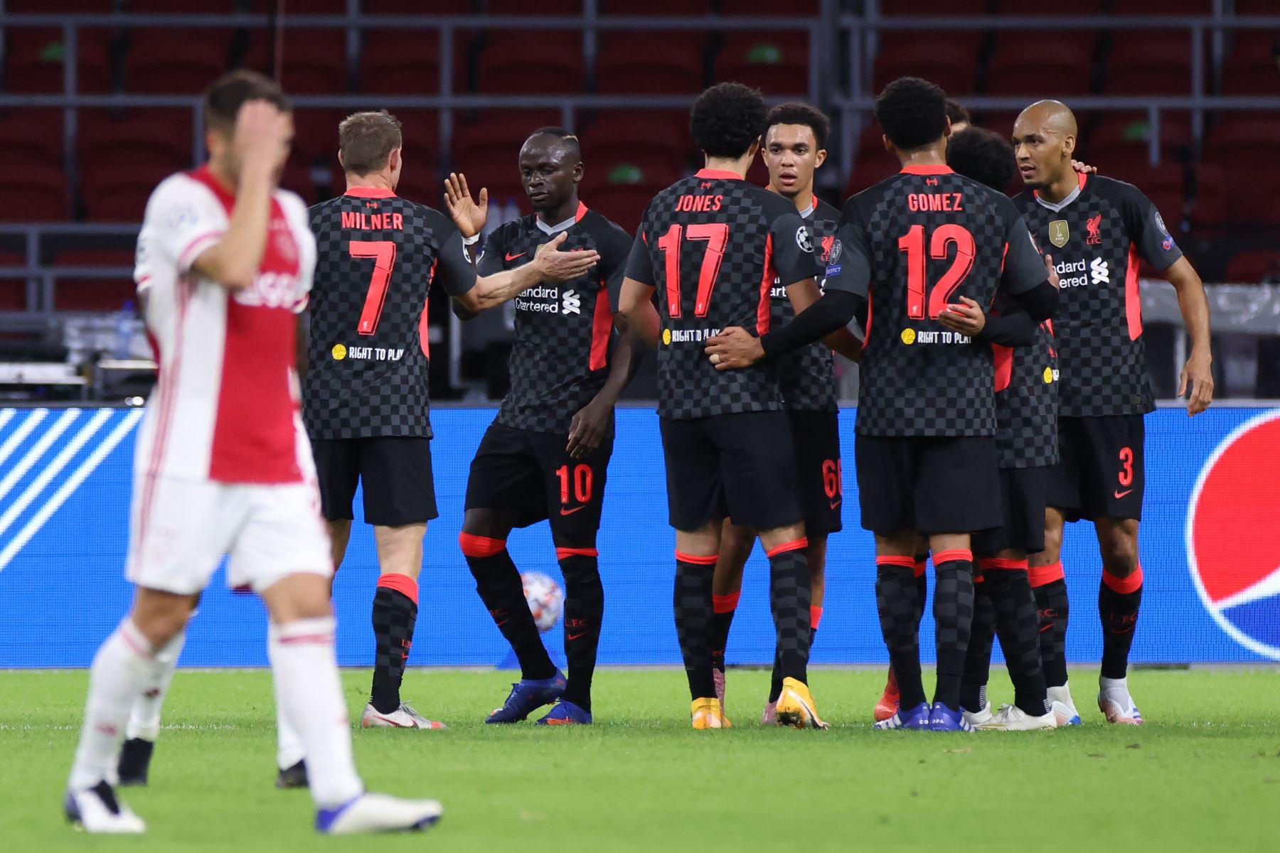 Los jugadores de Liverpool celebran después de que Ajax anotó un gol en propia meta durante el partido de fútbol de ida del Grupo D de la Liga de Campeones de la UEFA. Foto: AFP
