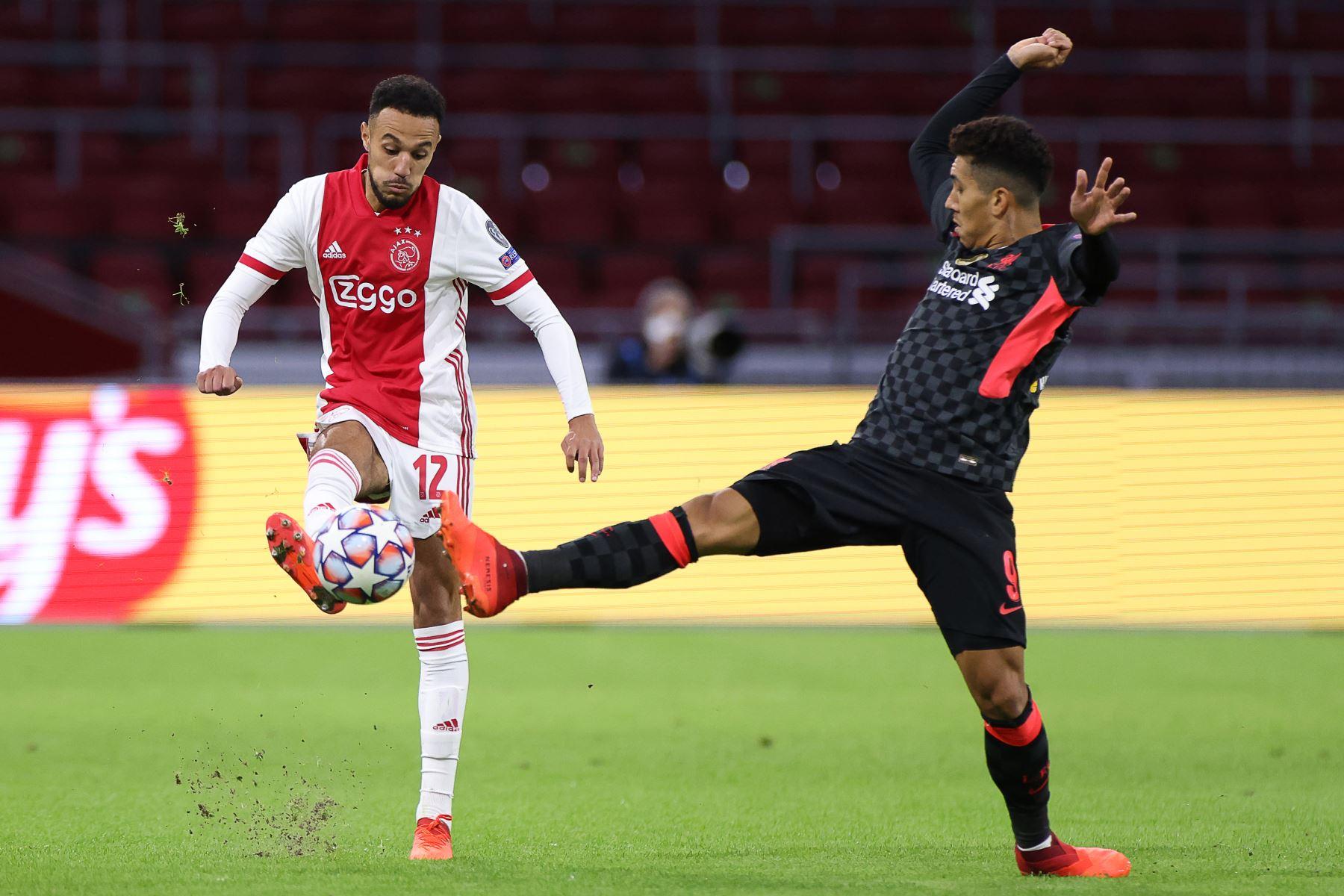 El defensor marroquí del Ajax Noussair Mazraoui compite por el balón con el delantero brasileño del Liverpool, Roberto Firmino, durante el partido de fútbol del Grupo D de la Liga de Campeones de la UEFA. Foto: AFP
