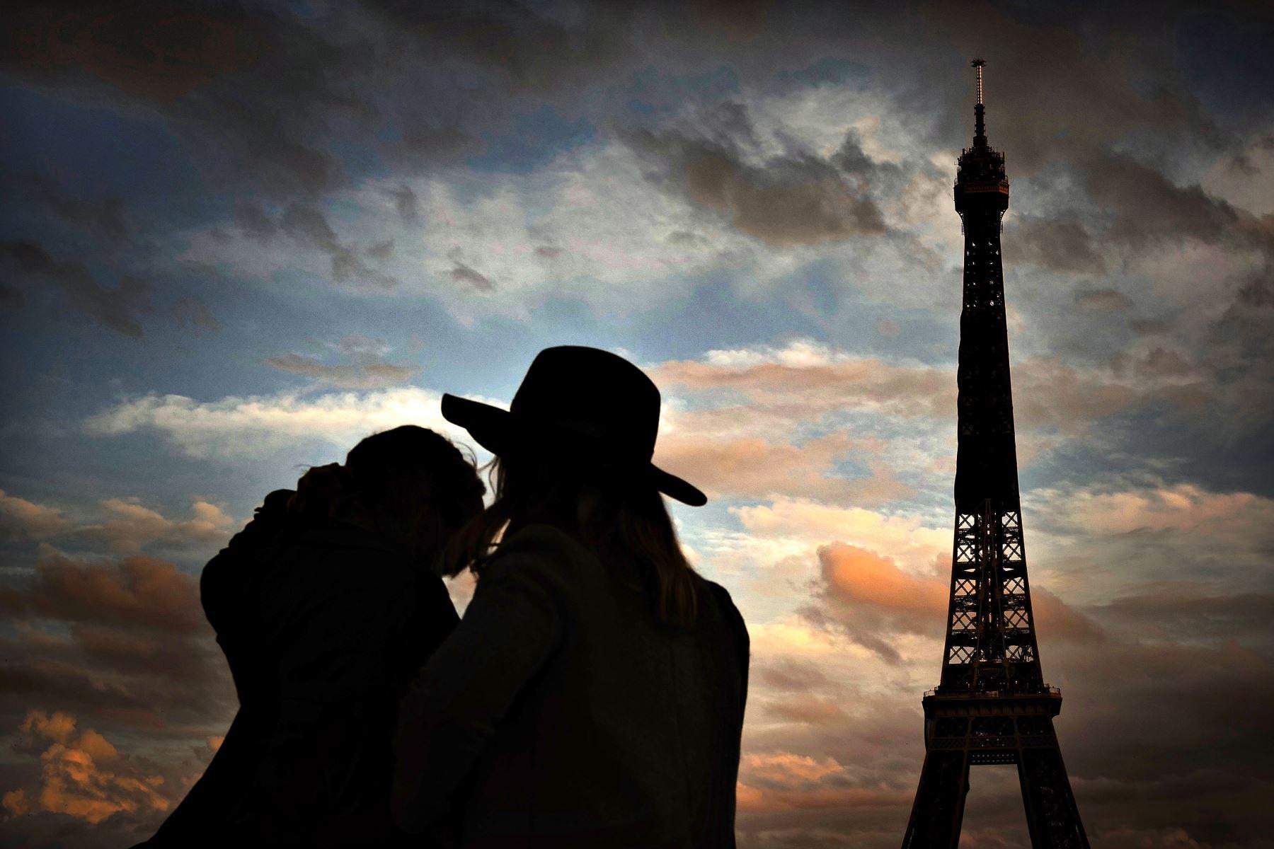 Dos personas frente a la Torre Eiffel en París, durante el toque de queda nocturno como medida contra la propagación de la pandemia Covid-19 causada por el nuevo coronavirus.  Foto: AFP