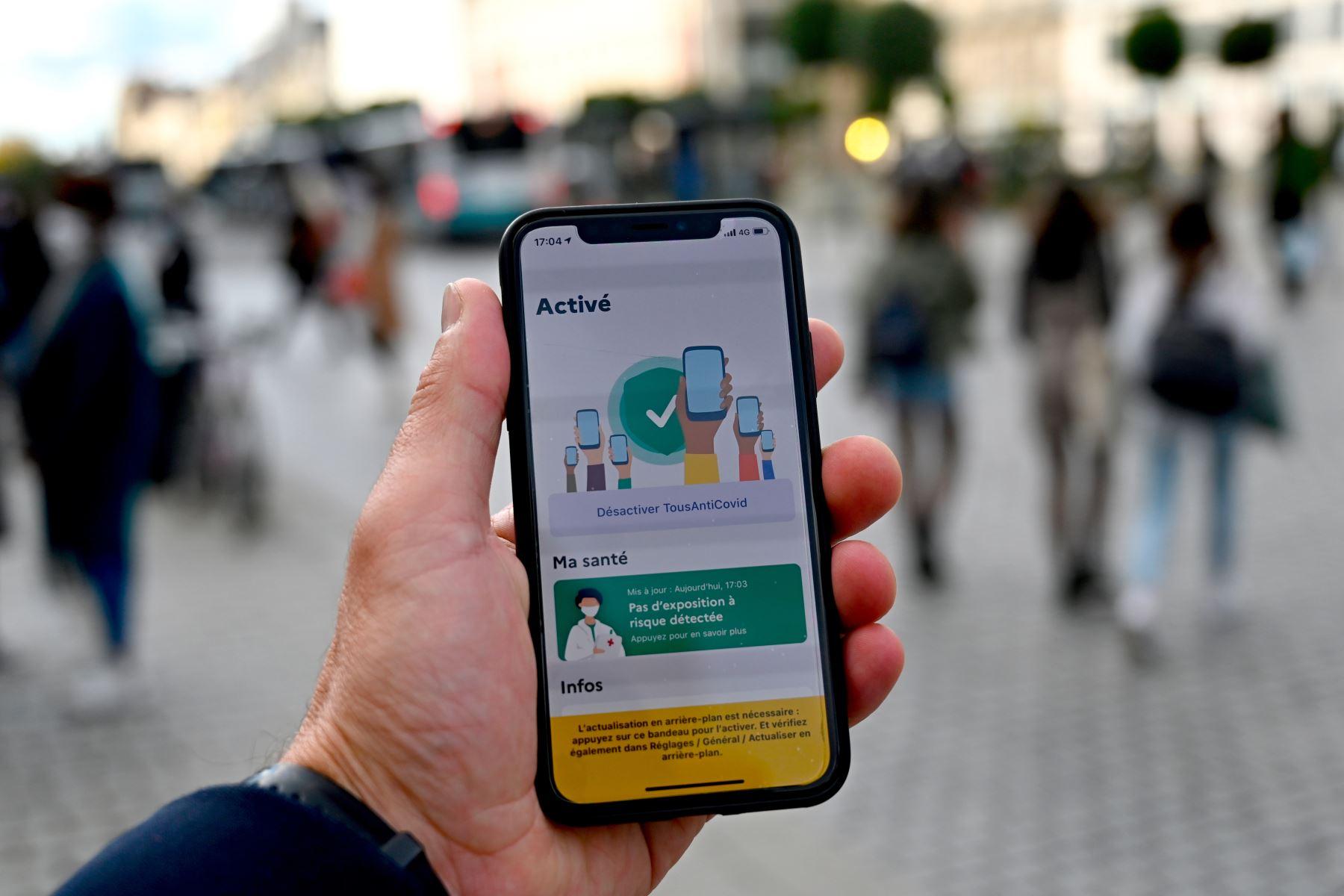 """Una persona sostiene un teléfono inteligente que muestra la nueva aplicación """"TousAntiCovid"""" en Rennes, oeste de Francia, ya que varios departamentos se pusieron en """"alerta máxima"""" y se implementaron nuevas medidas de toque de queda para frenar la propagación del Covid. -19  Foto: AFP"""