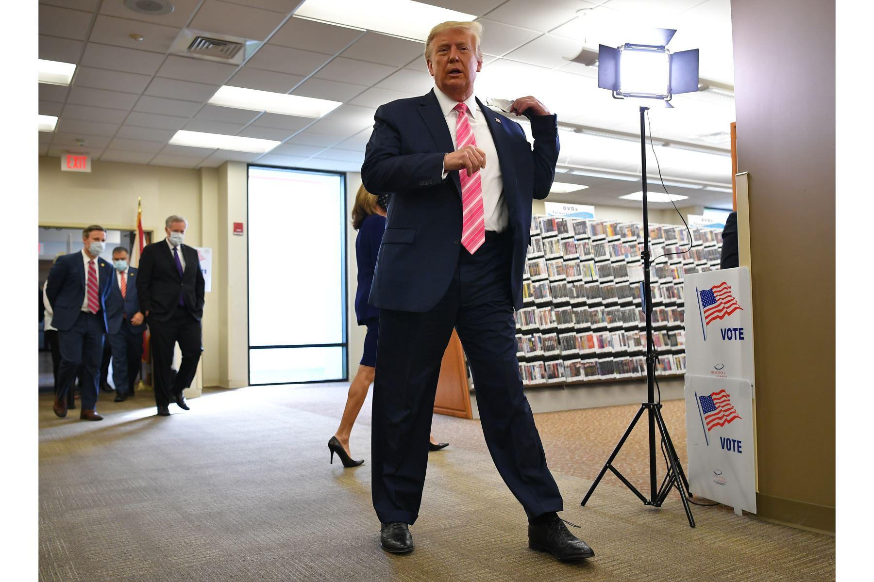 El presidente de los Estados Unidos, Donald Trump, se retira la mascarilla tras emitir su voto colegio electoral para emitir su voto en la Biblioteca Pública del Condado de Palm Beach, durante la votación anticipada para las elecciones del 3 de noviembre, en West Palm Beach, Florida. Foto: AFP