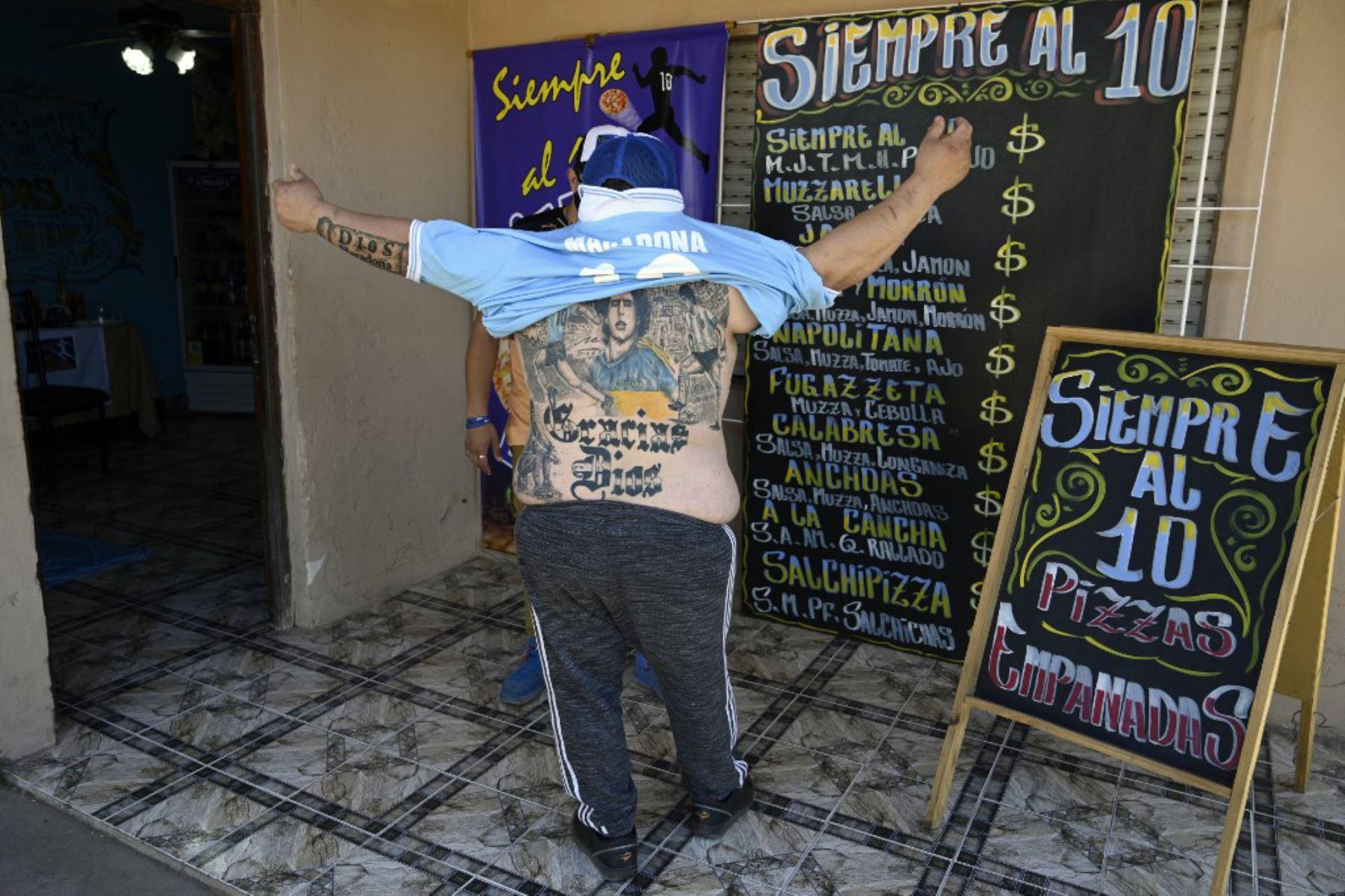 """El pizzero Guillermo Rodríguez, bautizado en la iglesia Maradoniana, muestra los tatuajes en su espalda que representan a la leyenda del fútbol argentino Diego Maradona, en su pizzería llamada """"Siempre al 10"""" (Siempre al 10), en referencia al número de la ex camiseta de su ídolo. , en Merlo, provincia de Buenos Aires. Rodríguez se hizo este tatuaje para conmemorar el 60 cumpleaños del actual entrenador de Gimnasia y Esgrima, que será el próximo 30 de octubre.  Foto: AFP"""