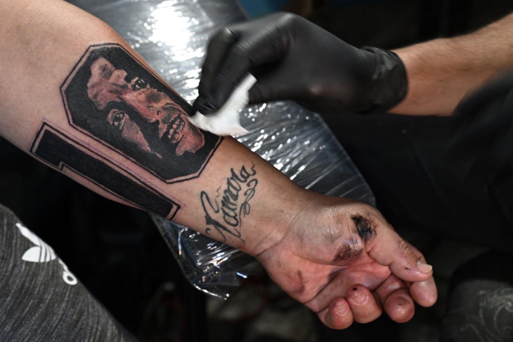 """El pizzero Guillermo Rodríguez, bautizado en la iglesia maradoniana, tiene un nuevo tatuaje con una imagen de la leyenda del fútbol argentino Diego Maradona realizado por el tatuador Juan Rojas, en su pizzería llamada """"Siempre al 10"""". Rodríguez se hizo este tatuaje para conmemorar al actual entrenador del 60 cumpleaños de Gimnasia y Esgrima, que será el próximo 30 de octubre.   Foto: AFP"""