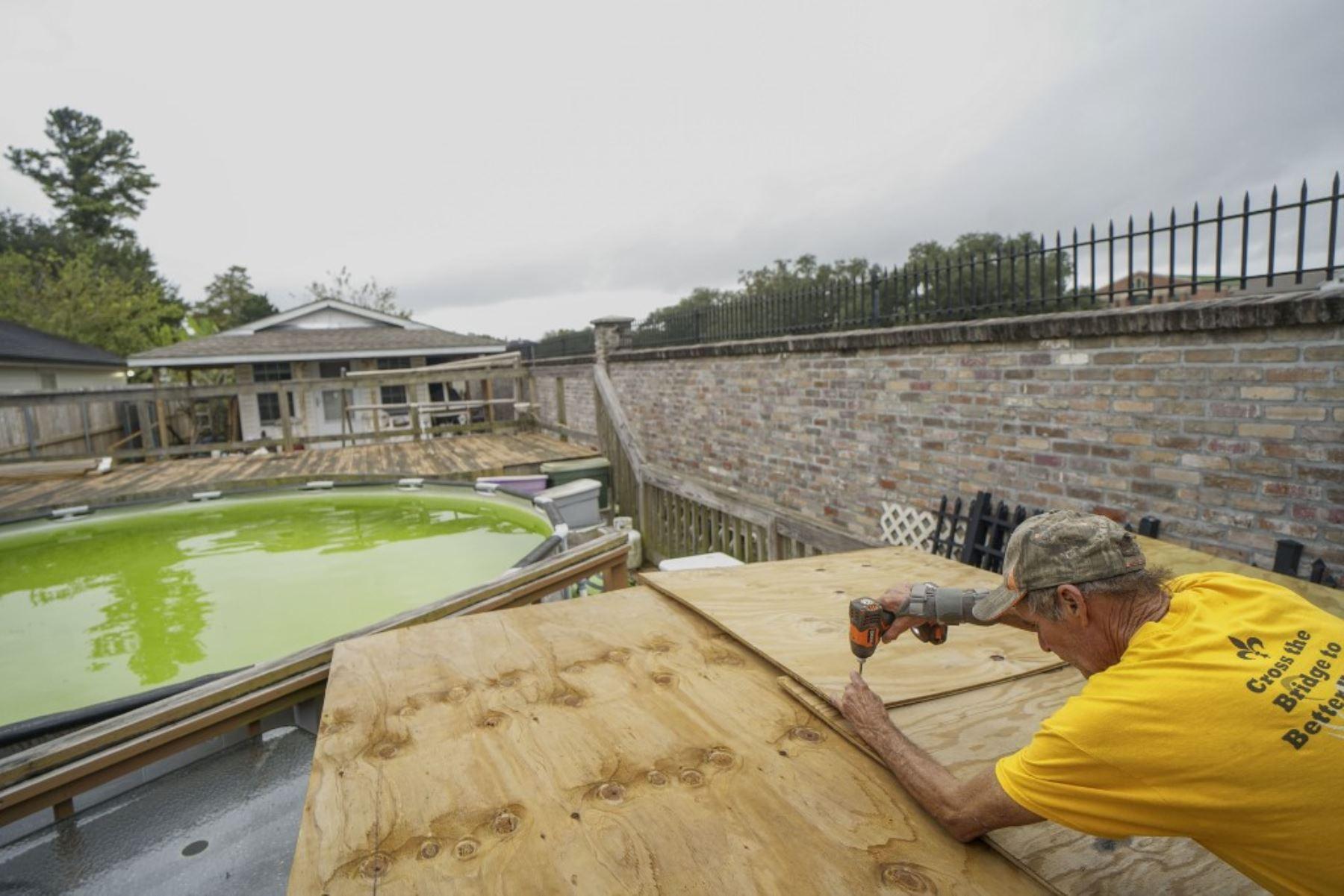 Will Schwander atornilla un refugio de madera contrachapada para proteger los muebles del patio cuando se acerca el huracán Zeta  en Arabi Luisiana.Foto:AFP