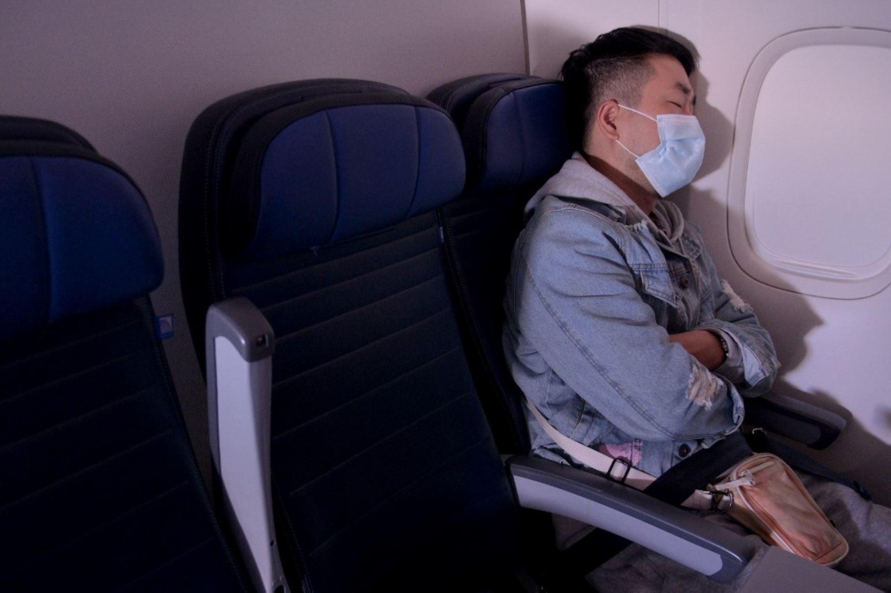 Se ve a un pasajero enmascarado durmiendo en un vuelo de San Francisco, California a Newark, Nueva Jersey. Foto: AFP