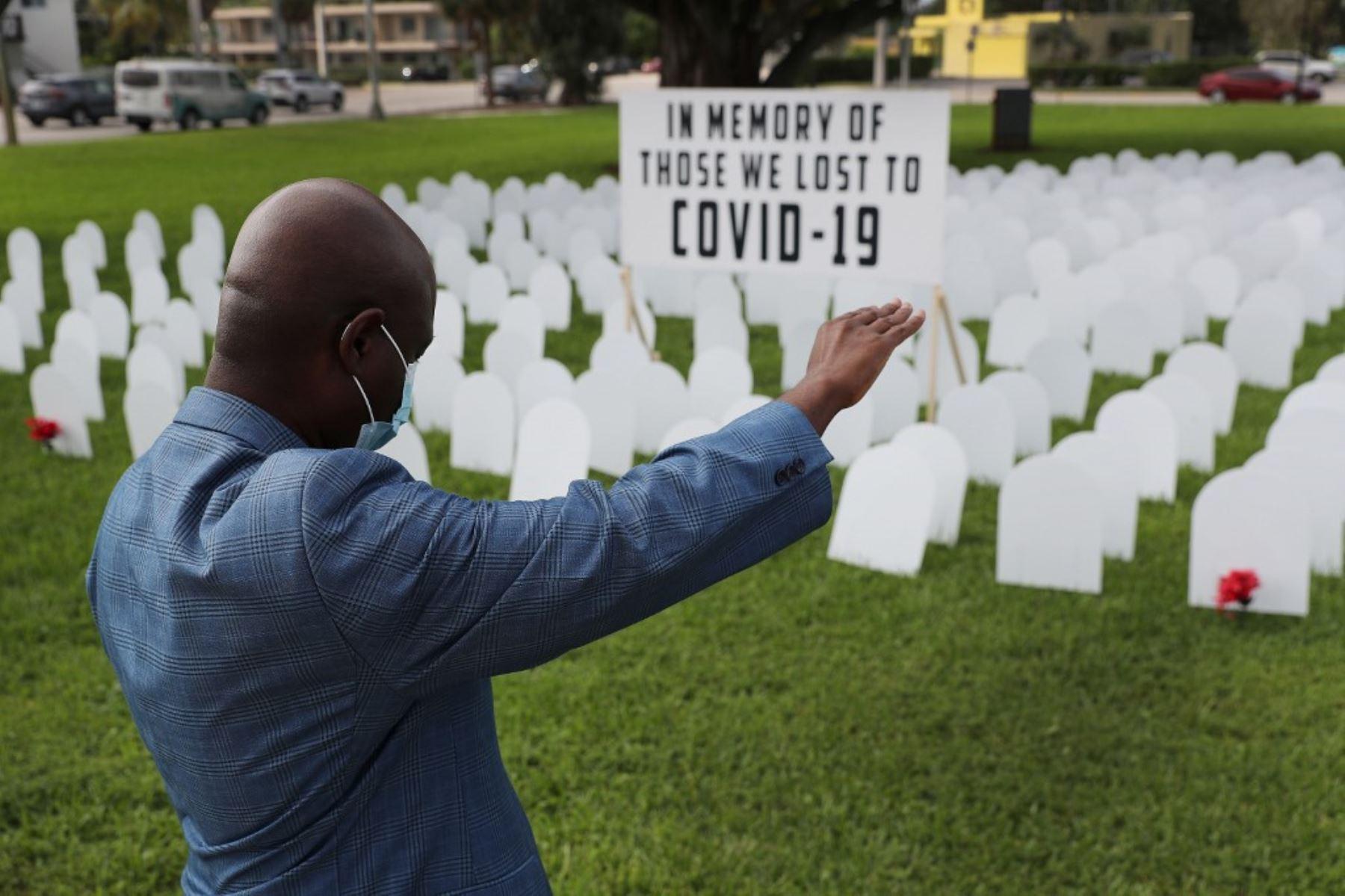 El vicealcalde Alix Desulme, de la ciudad de North Miami, levanta el brazo durante una oración por las vidas locales perdidas por COVID-19 mientras se presenta un monumento a los perdidos en Griffing Park.Foto: AFP