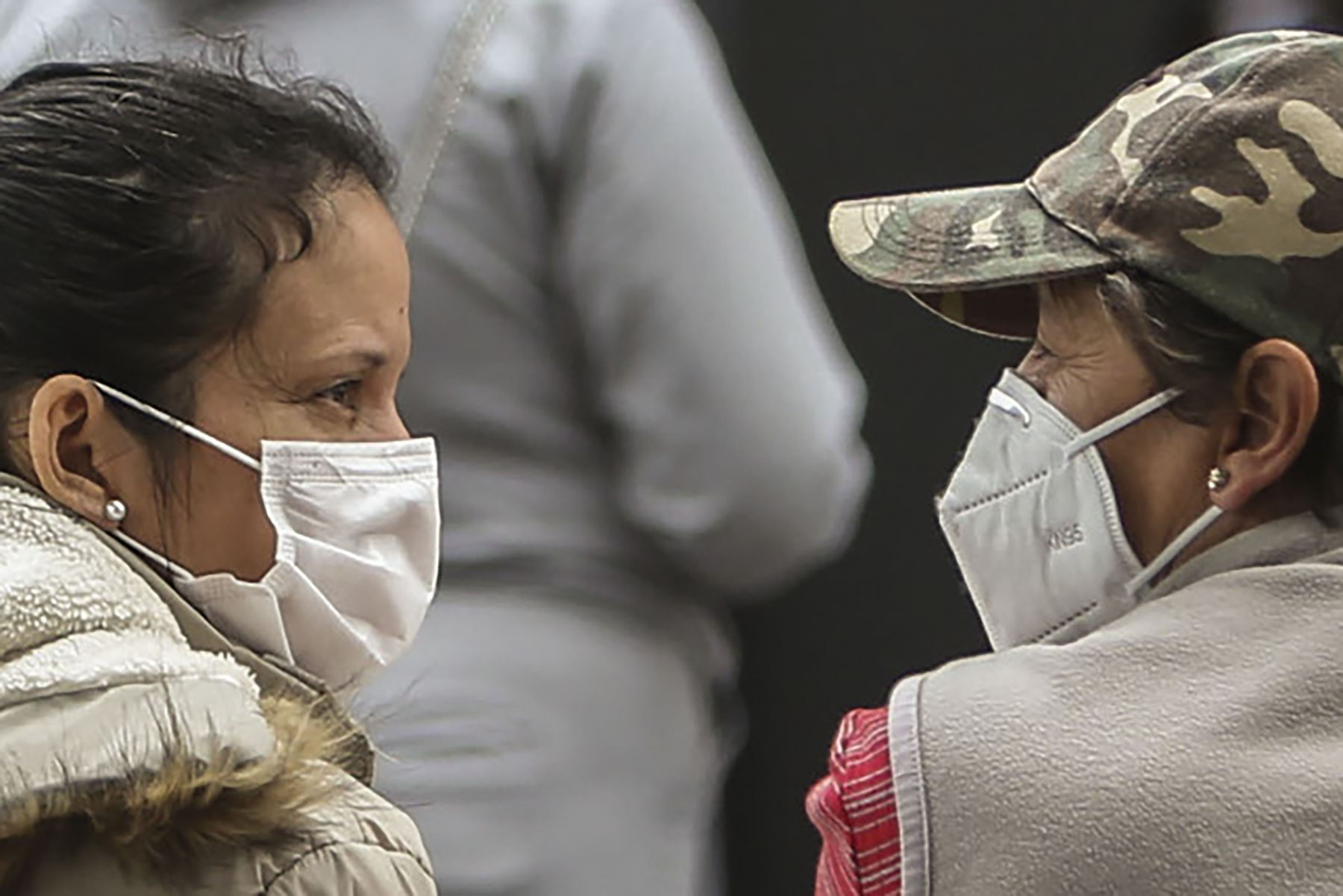 Mujeres con mascarilla hablan afuera de una carpa donde se atiende a pacientes con síntomas de covid-19, afuera del hospital IESS Sur, en Quito, el 20 de julio del 2020. Foto: AFP.