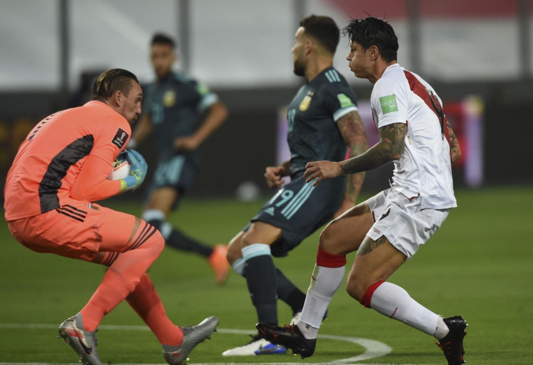 El arquero argentino Franco Armani atrapa el balón junto al peruano Gianluca Lapadula durante su partido de fútbol a puertas cerradas clasificatorio sudamericano para la Copa Mundial de la FIFA 2022 en el Estadio Nacional de Lima. Foto: AFP
