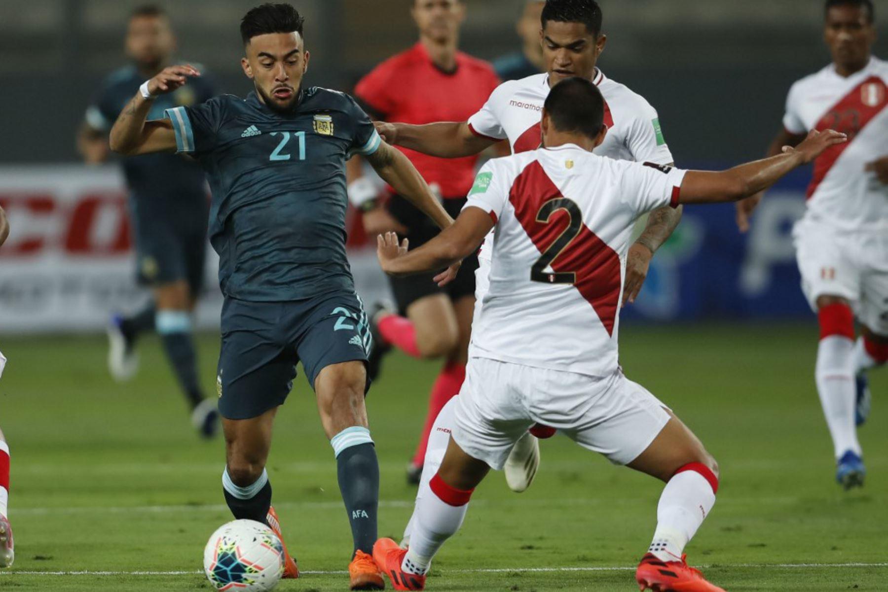 El argentino Nicolás González y el peruano Luis Abram compiten por el balón durante su partido de fútbol a puerta cerrada clasificatorio sudamericano para la Copa Mundial de la FIFA 2022 en el Estadio Nacional de Lima. Foto: AFP