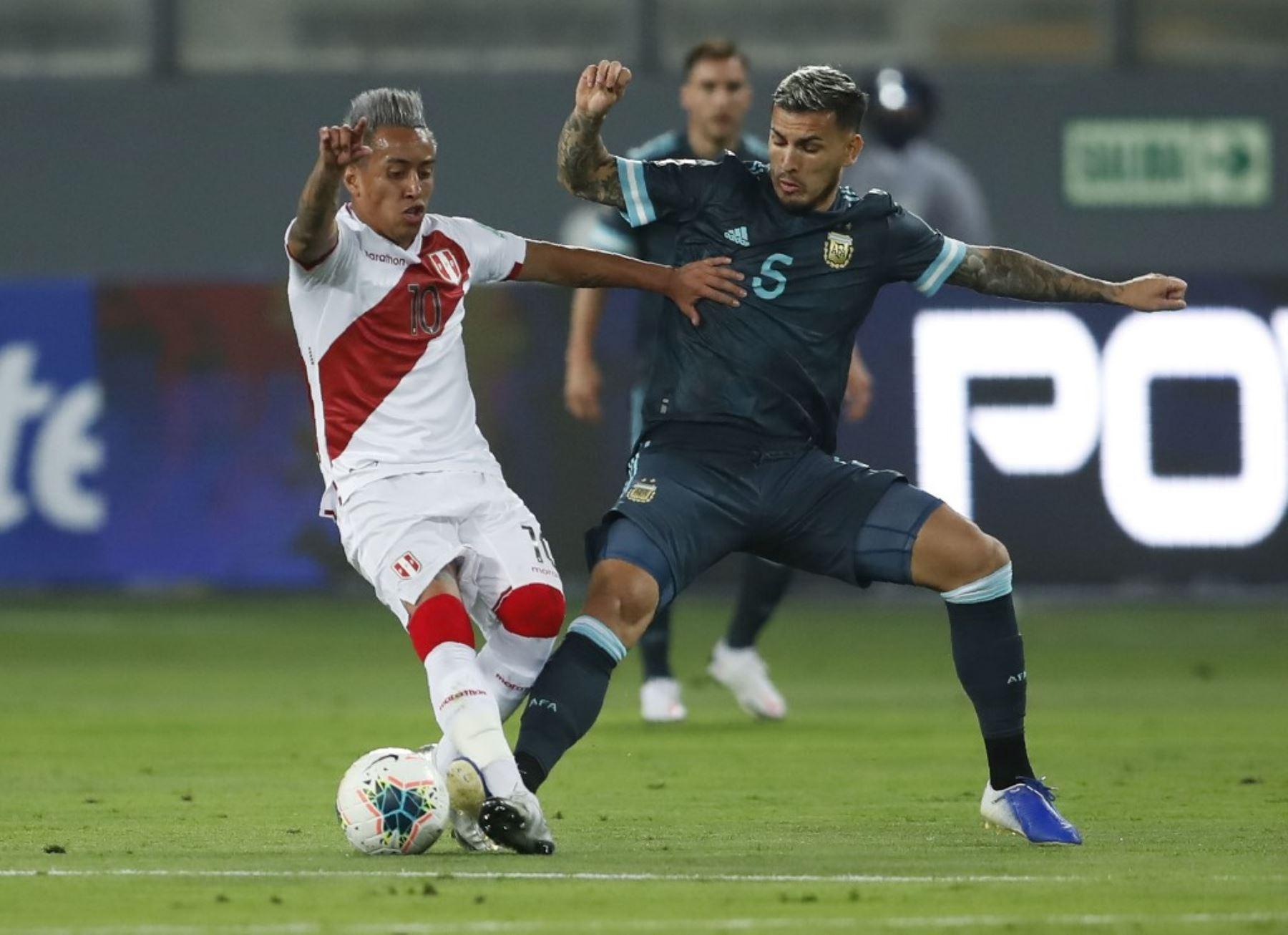 El peruano Christian Cueva (izq.) Y el argentino Leandro Paredes compiten por el balón durante su partido de fútbol a puerta cerrada clasificatorio sudamericano para la Copa Mundial de la FIFA 2022 en el Estadio Nacional de Lima. Foto: AFP