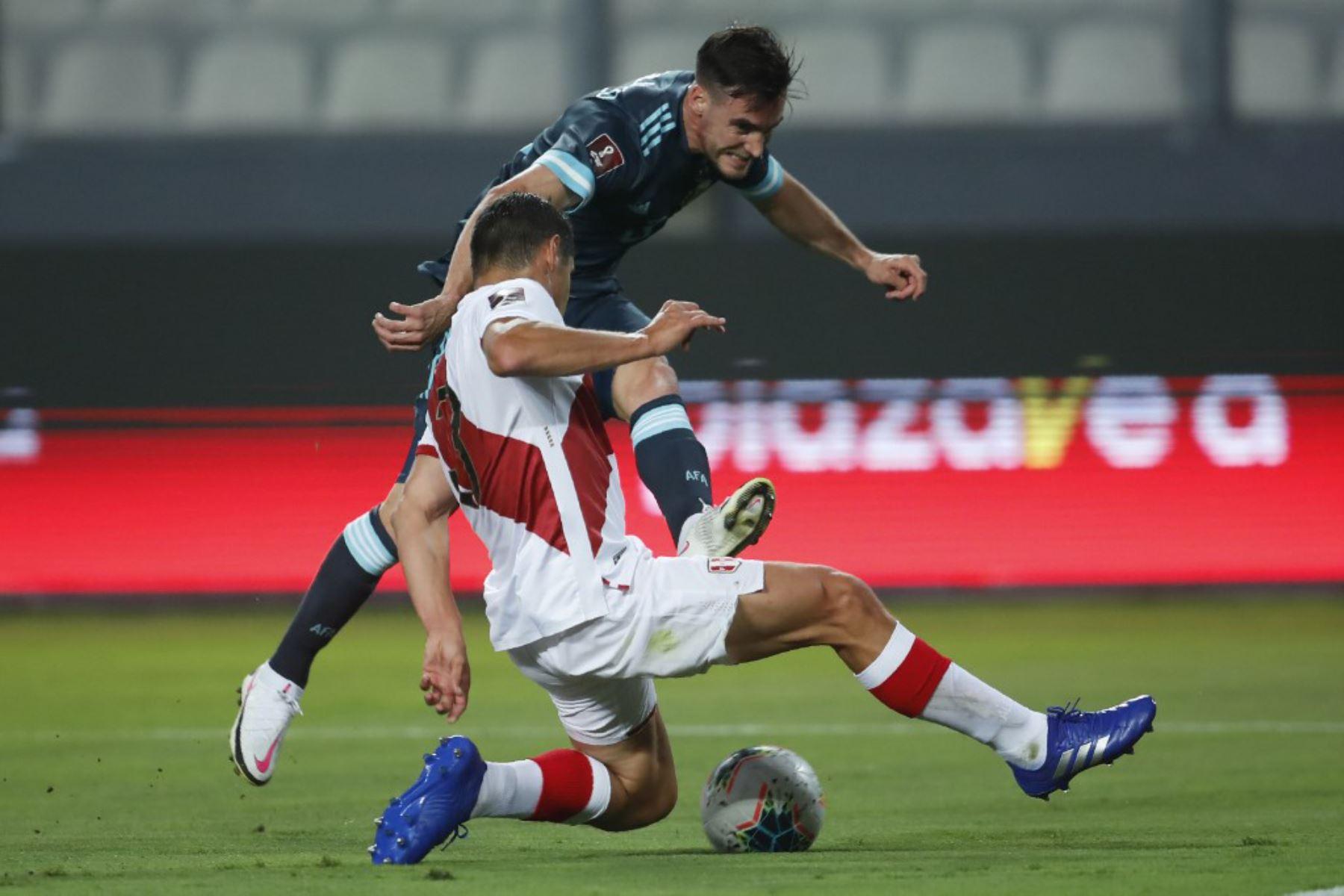 El argentino Nicolás Tagliafico  y el peruano Aldo Corzo compiten por el balón durante su partido de fútbol a puerta cerrada clasificatorio sudamericano para la Copa Mundial de la FIFA 2022 en el Estadio Nacional. Foto: AFP