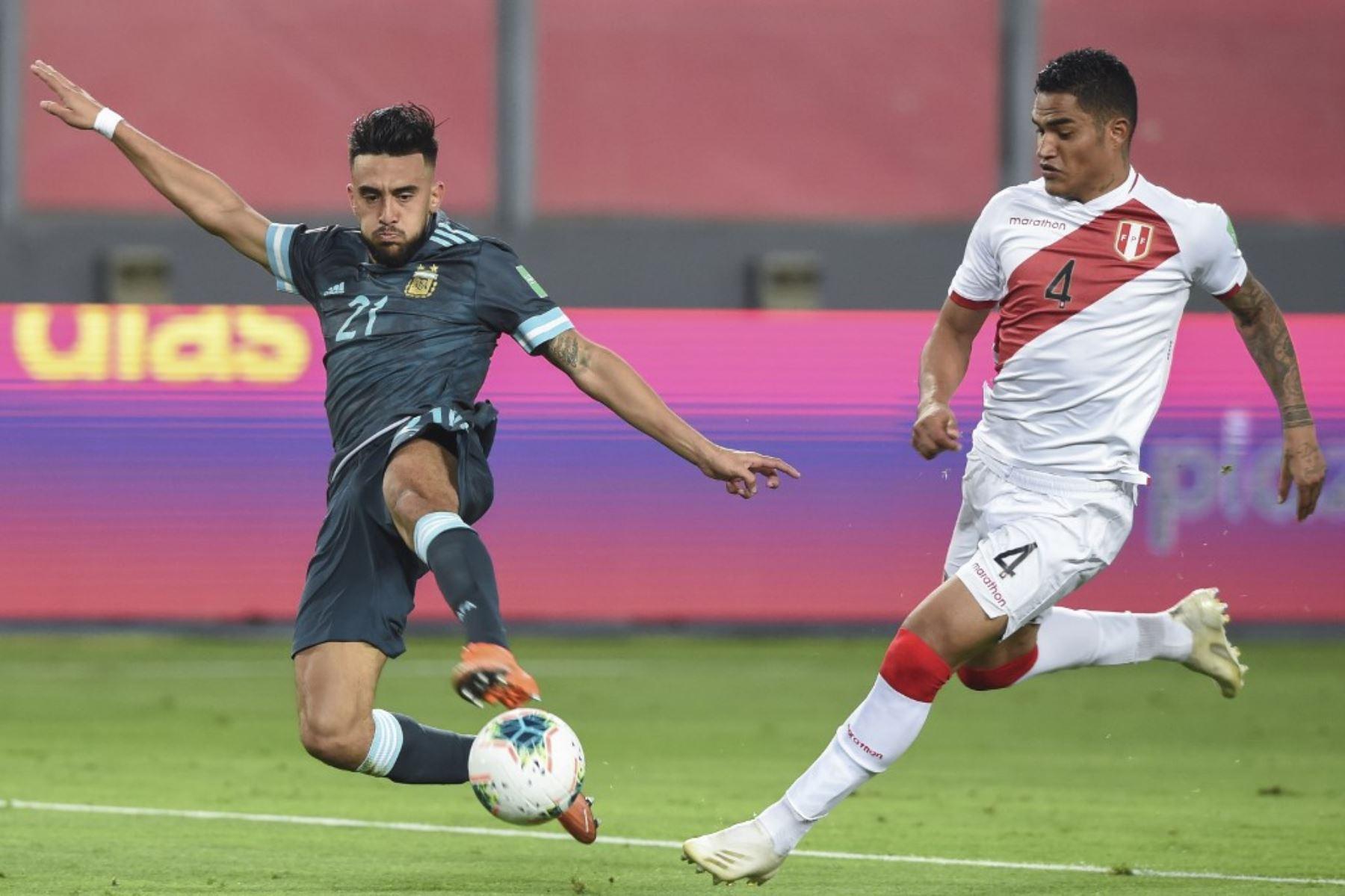 El argentino Nicolás González (izq.) Y el peruano Anderson Santamaría compiten por el balón durante su partido de fútbol a puerta cerrada clasificatorio sudamericano para la Copa Mundial de la FIFA 2022 en el Estadio Nacional de Lima. Foto: AFP