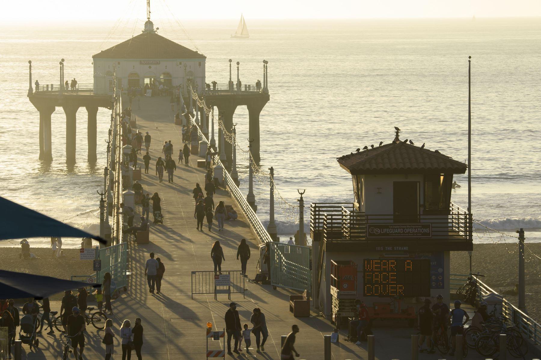 La gente camina en el muelle en Manhattan Beach, California, unas horas antes del inicio del nuevo toque de queda. Foto: AFP
