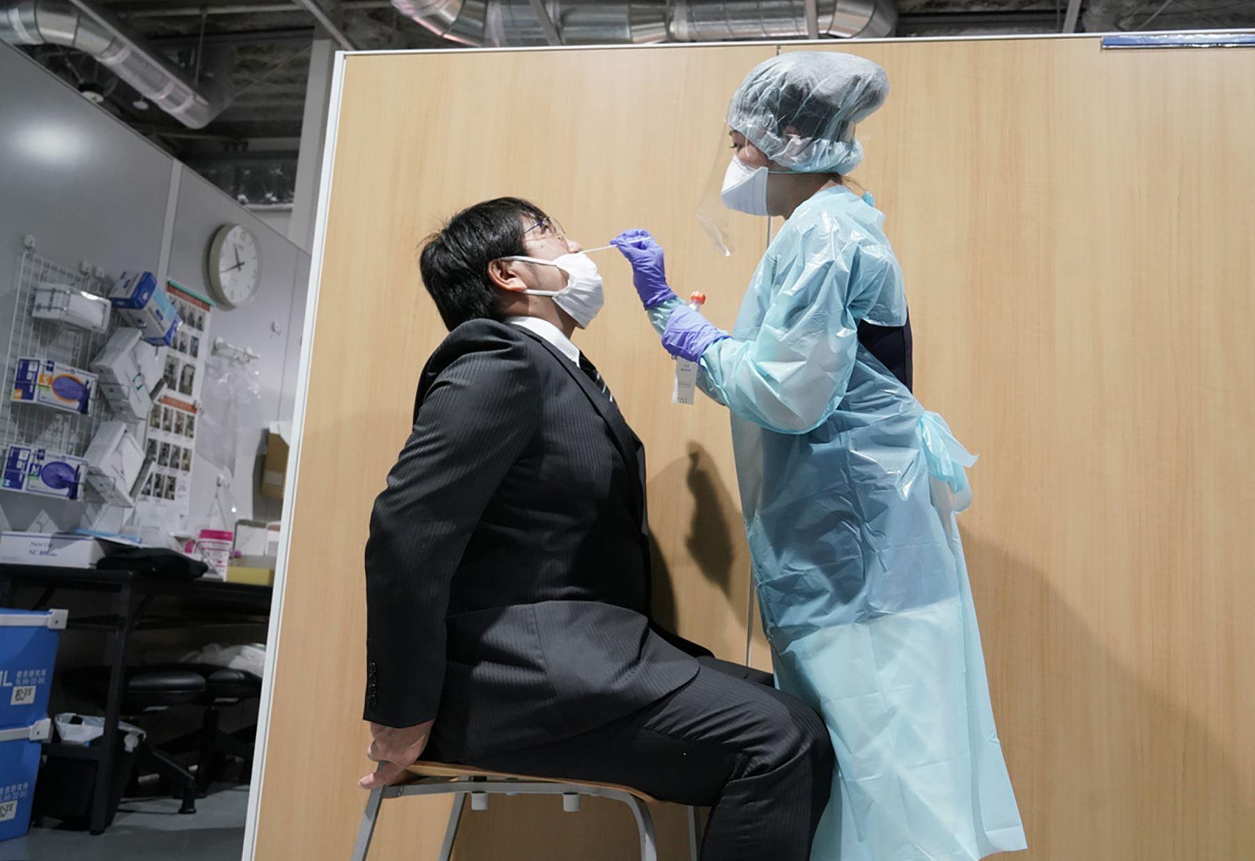 Un miembro del personal médico realiza una prueba del coronavirus en el centro de pruebas del aeropuerto de Narita, en Japón. Foto: AFP