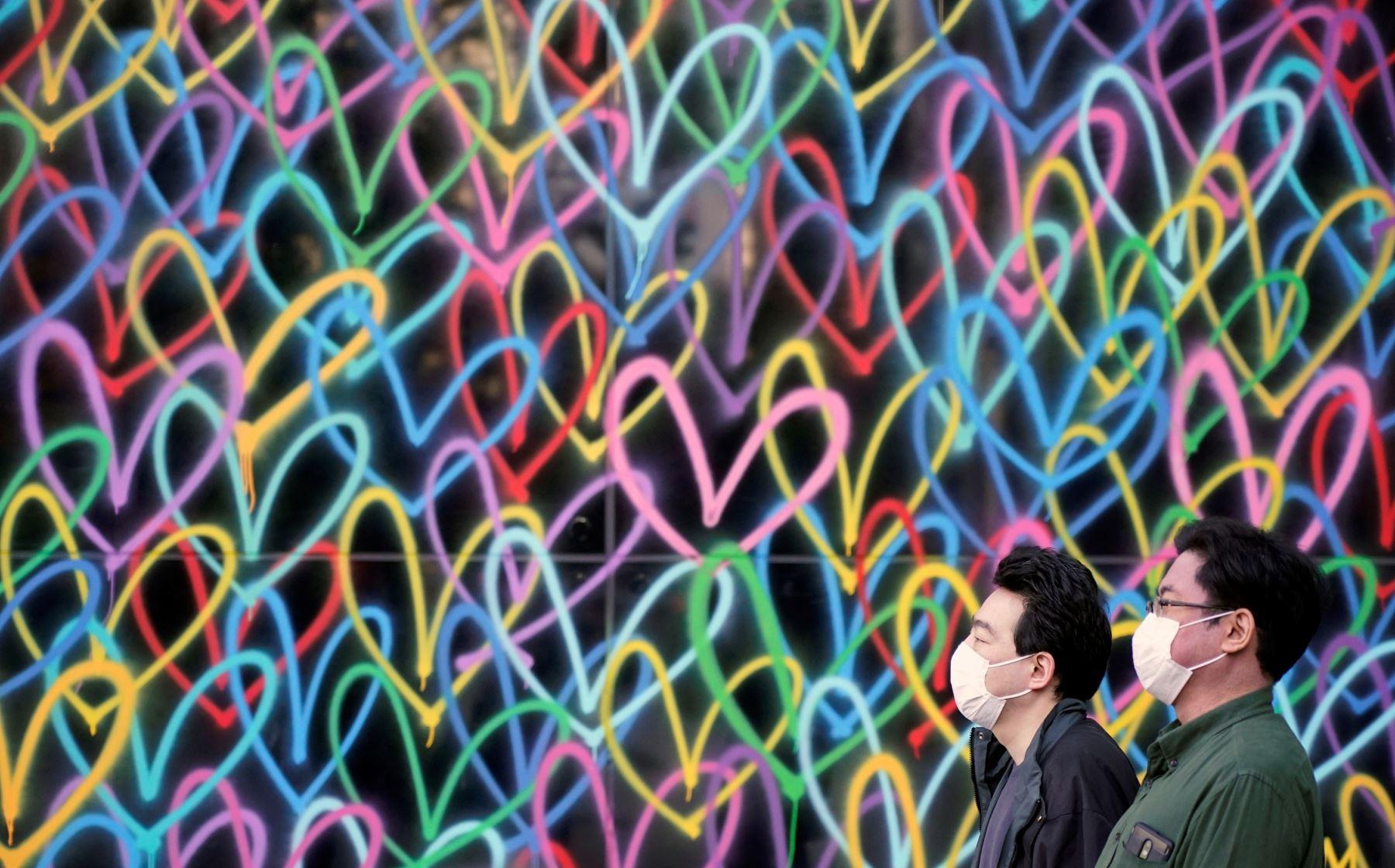 Los transeúntes con mascarillas pasan ante una pared pintada en un distrito de negocios en Tokio. Foto: EFE
